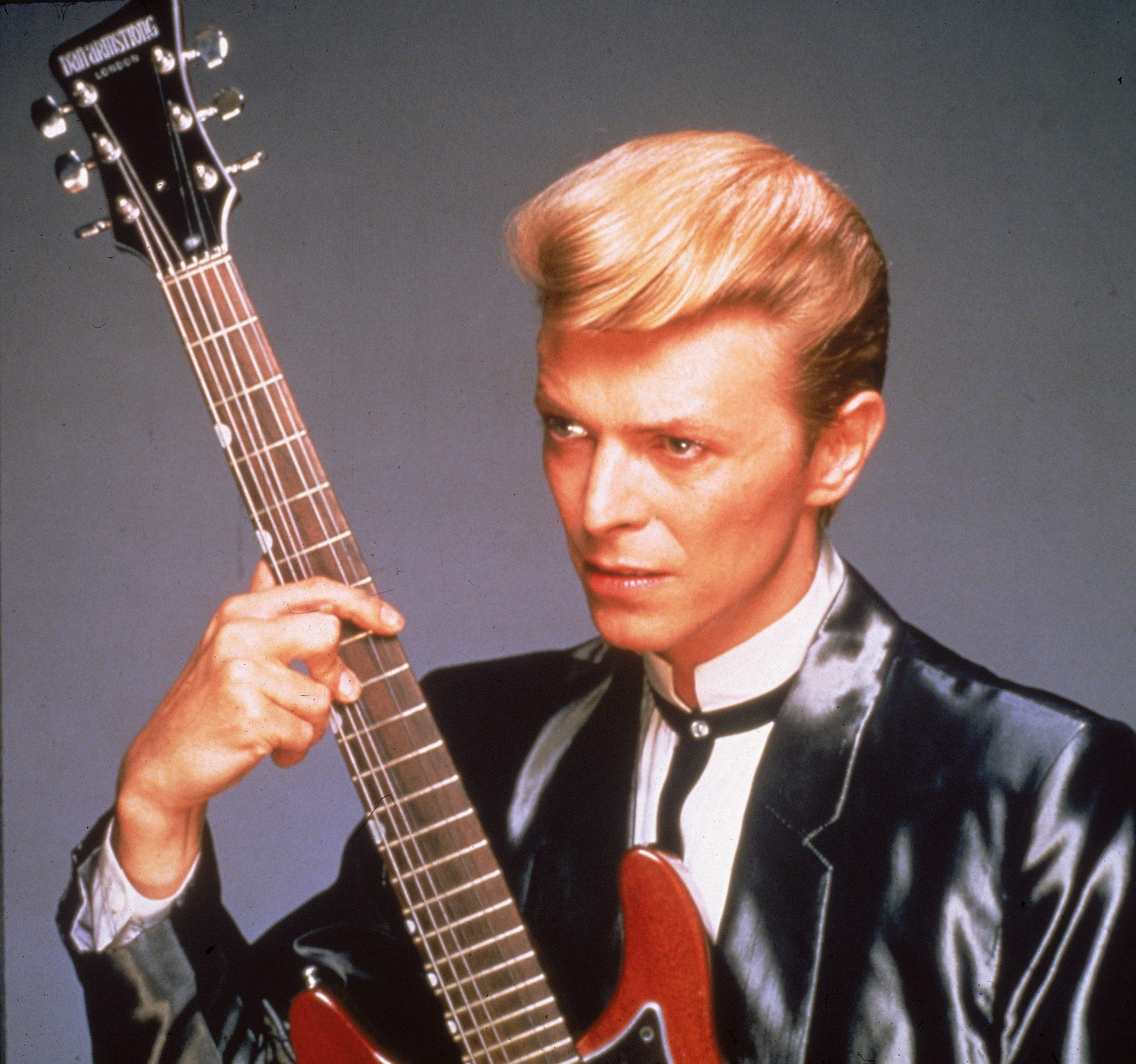 Studio portrait of British rock singer David Bowie wearing a black satin suit and holding a red guitar, 1980s.