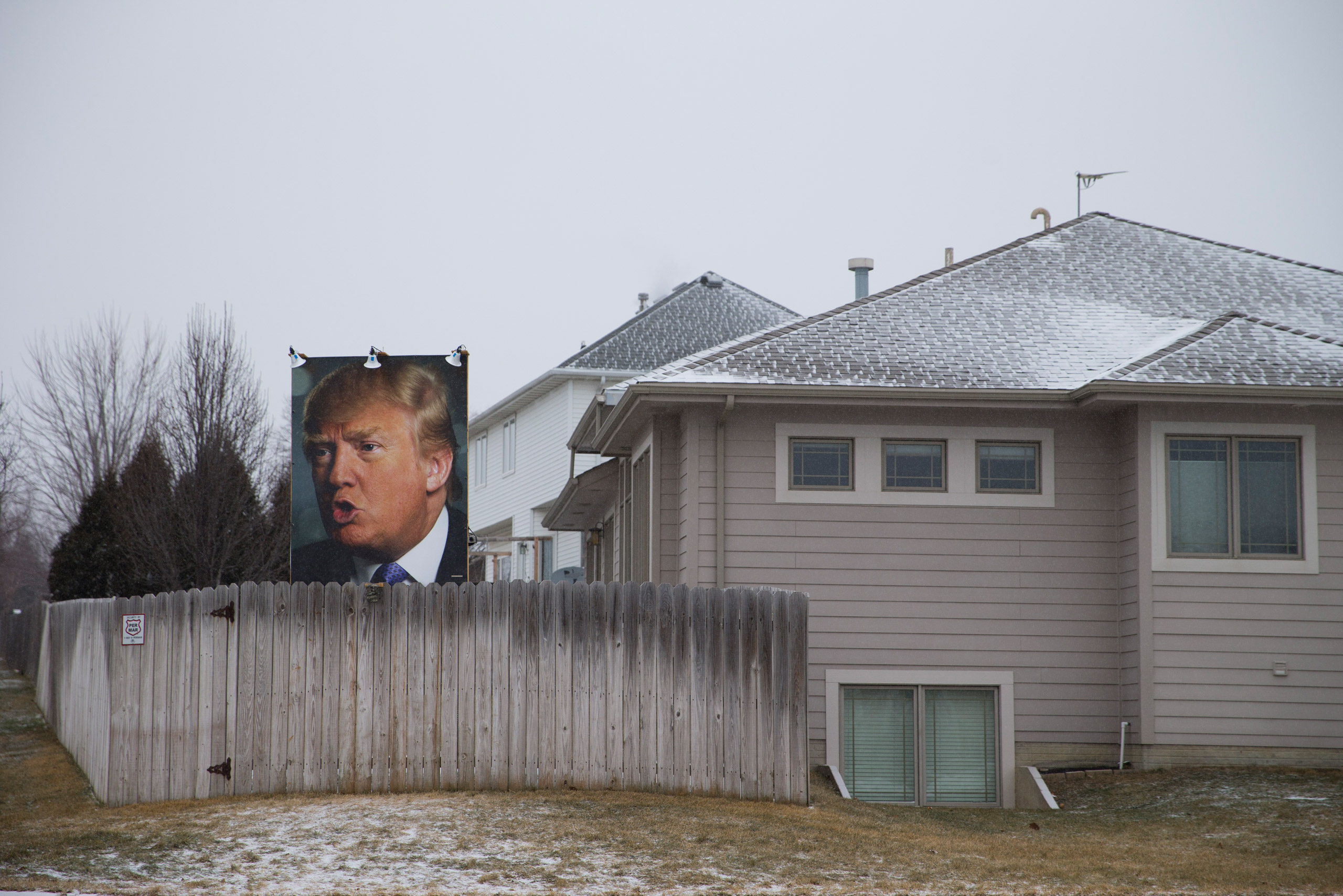 A photo of Republican presidential candidate Donald Trump hangs outside a home in West Des Moines, Iowa, on Jan. 19, 2016.
