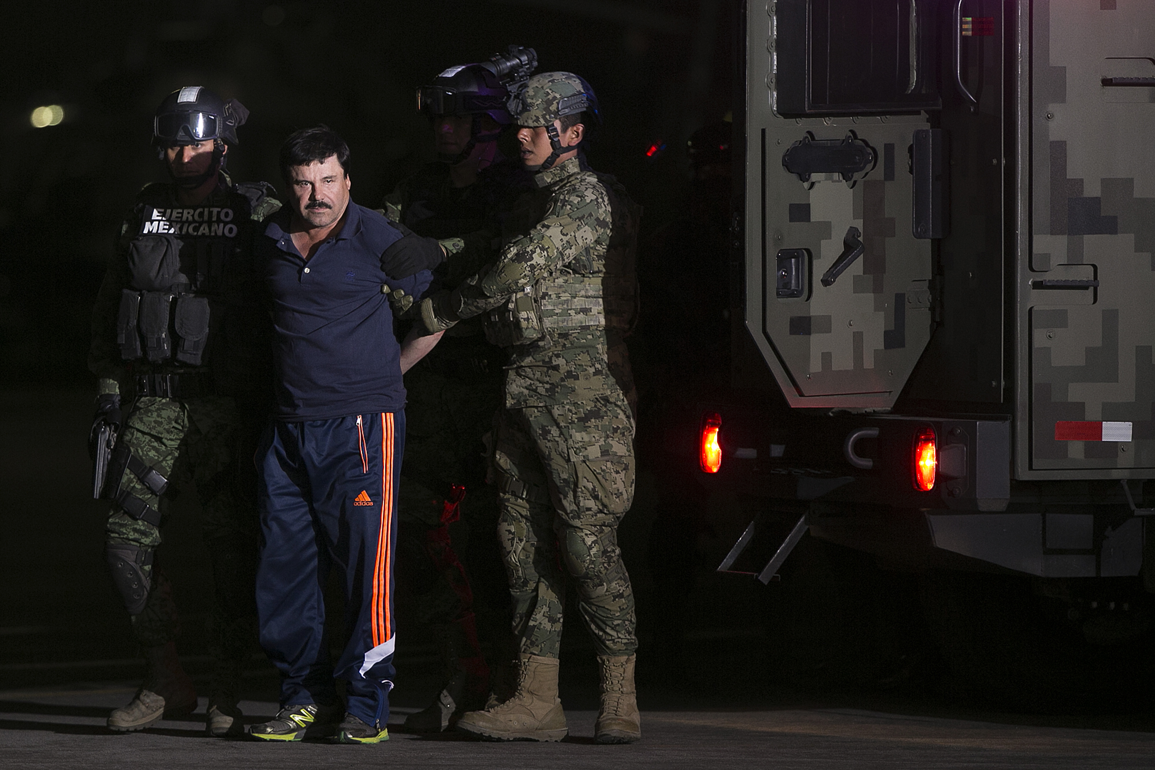 Joaquin Guzman, the world's most wanted-drug trafficker, second left, is escorted by Mexican security forces at a Navy hangar in Mexico City, Mexico, on Jan. 8, 2016.