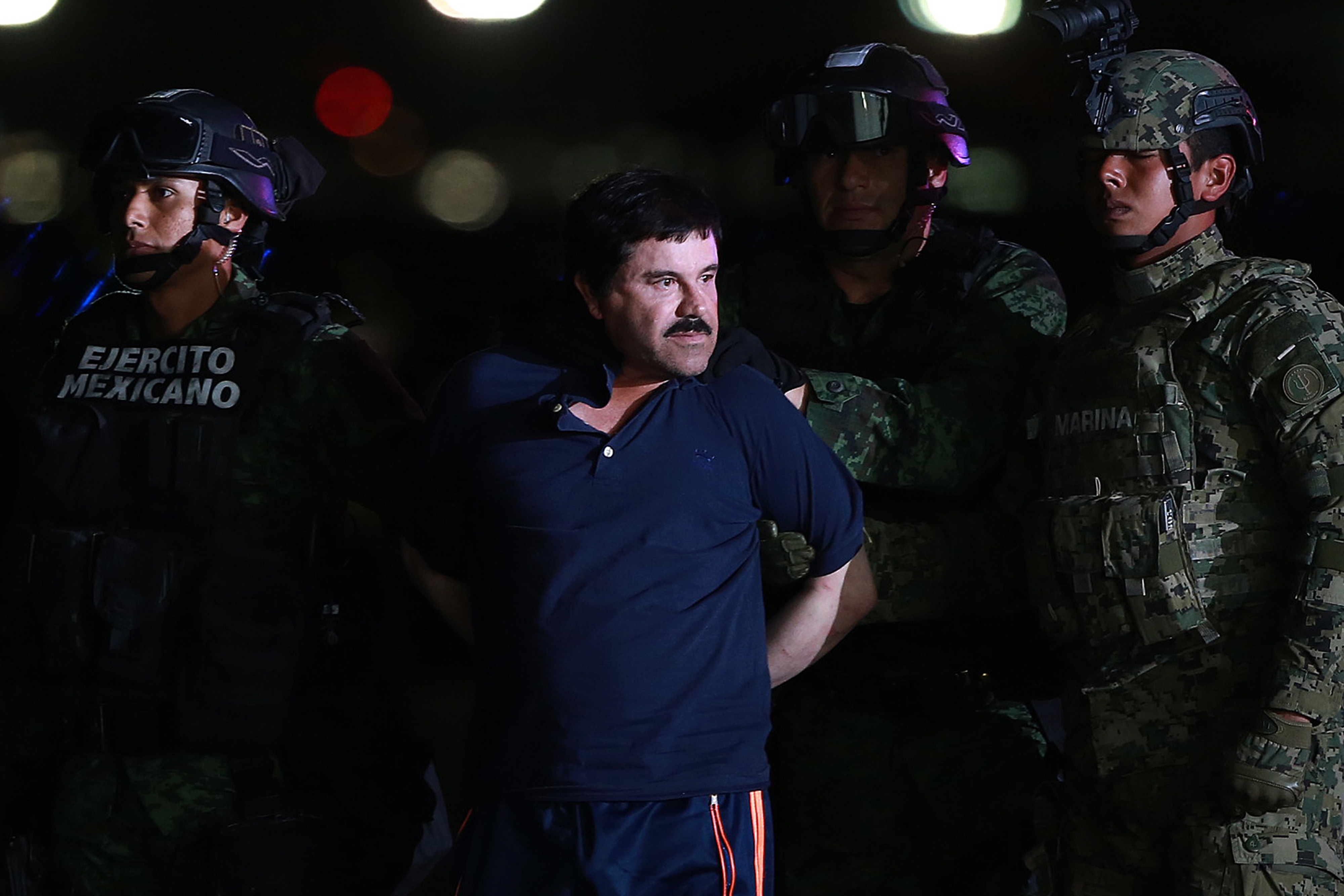 Joaquin Guzman, the world's most wanted-drug trafficker, center, is escorted by Mexican security forces at a Navy hangar in Mexico City, Mexico, on Jan. 8, 2016.