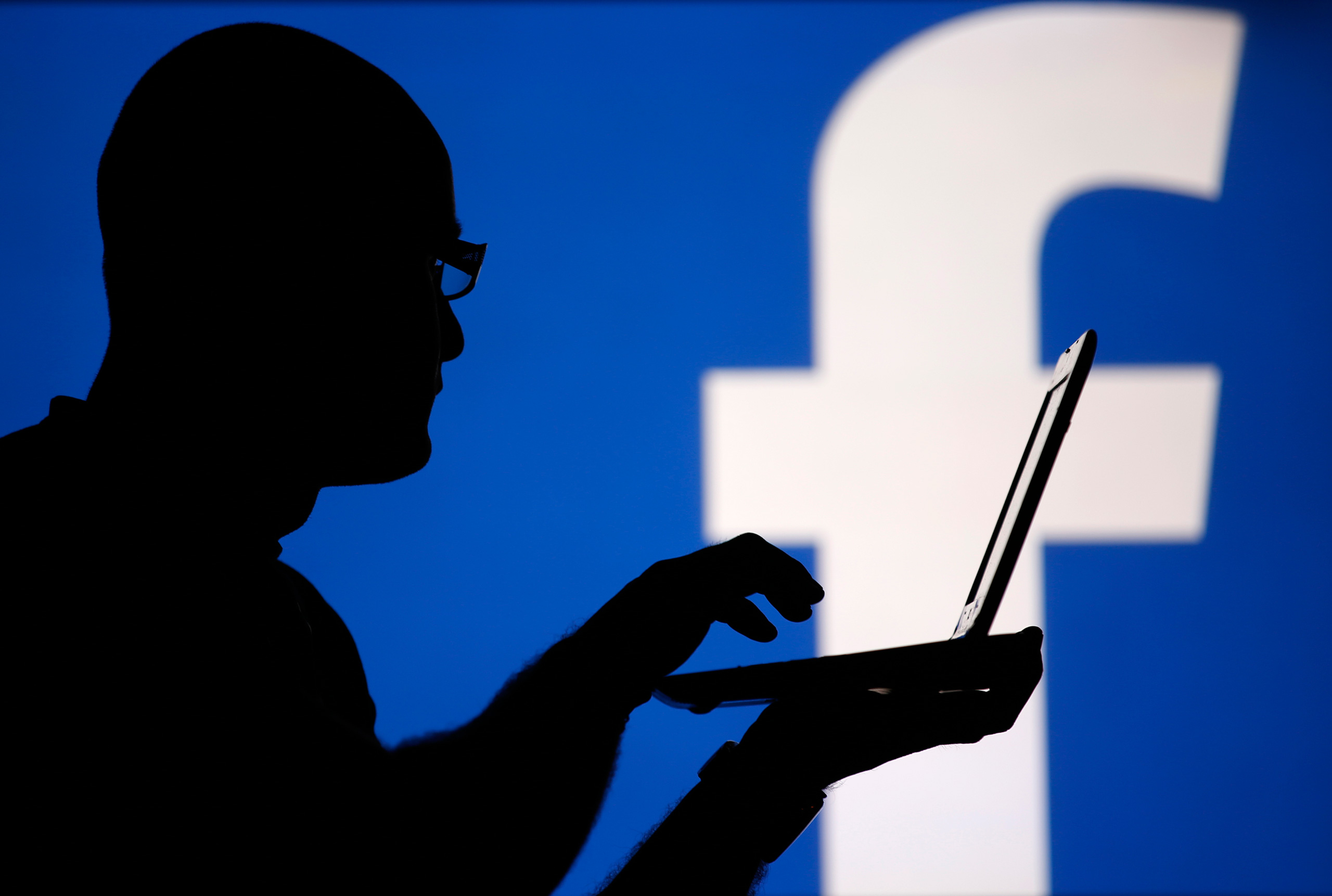 A man is silhouetted against a Facebook logo as he poses with a laptop in this photo illustration taken in Zenica, Bosnia, on Aug. 14, 2013.