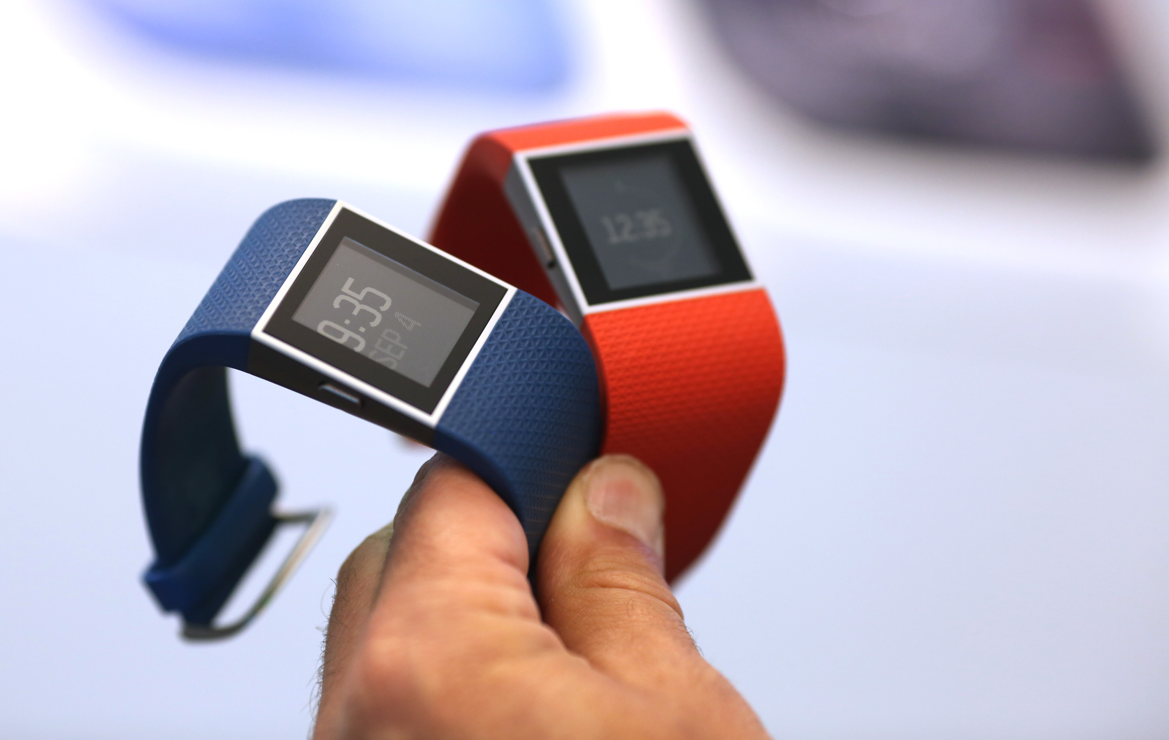 An employee holds Fitbit Inc. Surge smartwatches during the IFA International Consumer Electronics Show in Berlin, Germany, on Friday, Sept. 4, 2015.