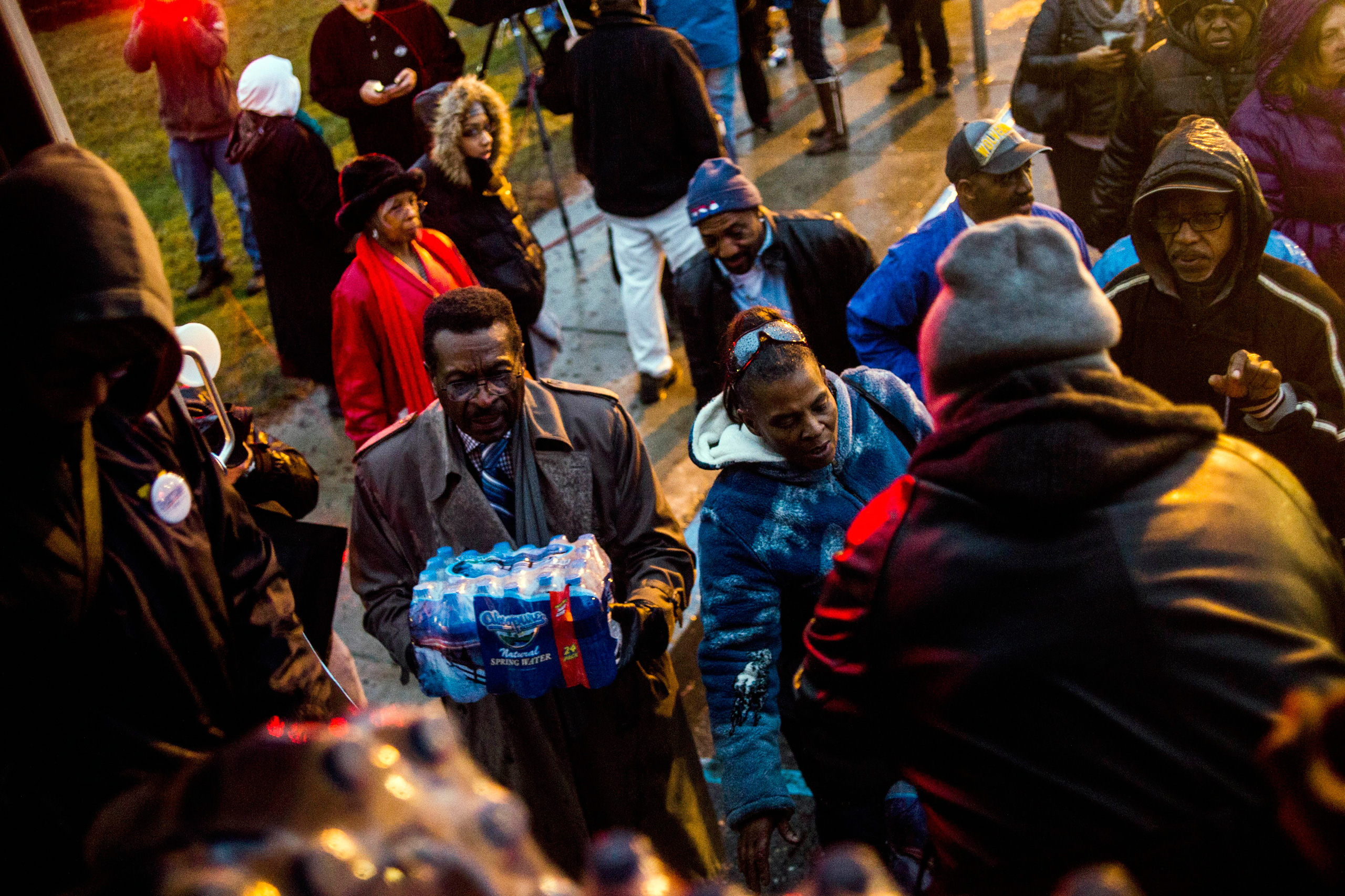 Flint residents line up for free bottled water as activists protest outside of City Hall to protest Michigan Gov. Rick Snyder's handling of the water crisis in Flint, Mich., on Jan. 8, 2016.
