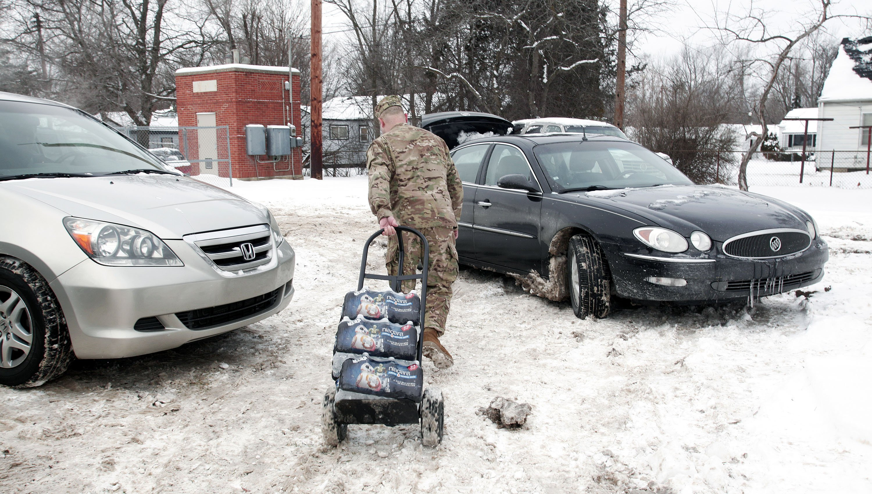 Michigan National Guard Staff Sergeant Steve Kiger of Beaverton, Michigan, helps Christine Brown of Flint, Michigan take bottled water out to her car after she received it at a Flint Fire Station on Jan 13, 2016 in Flint, Michigan.