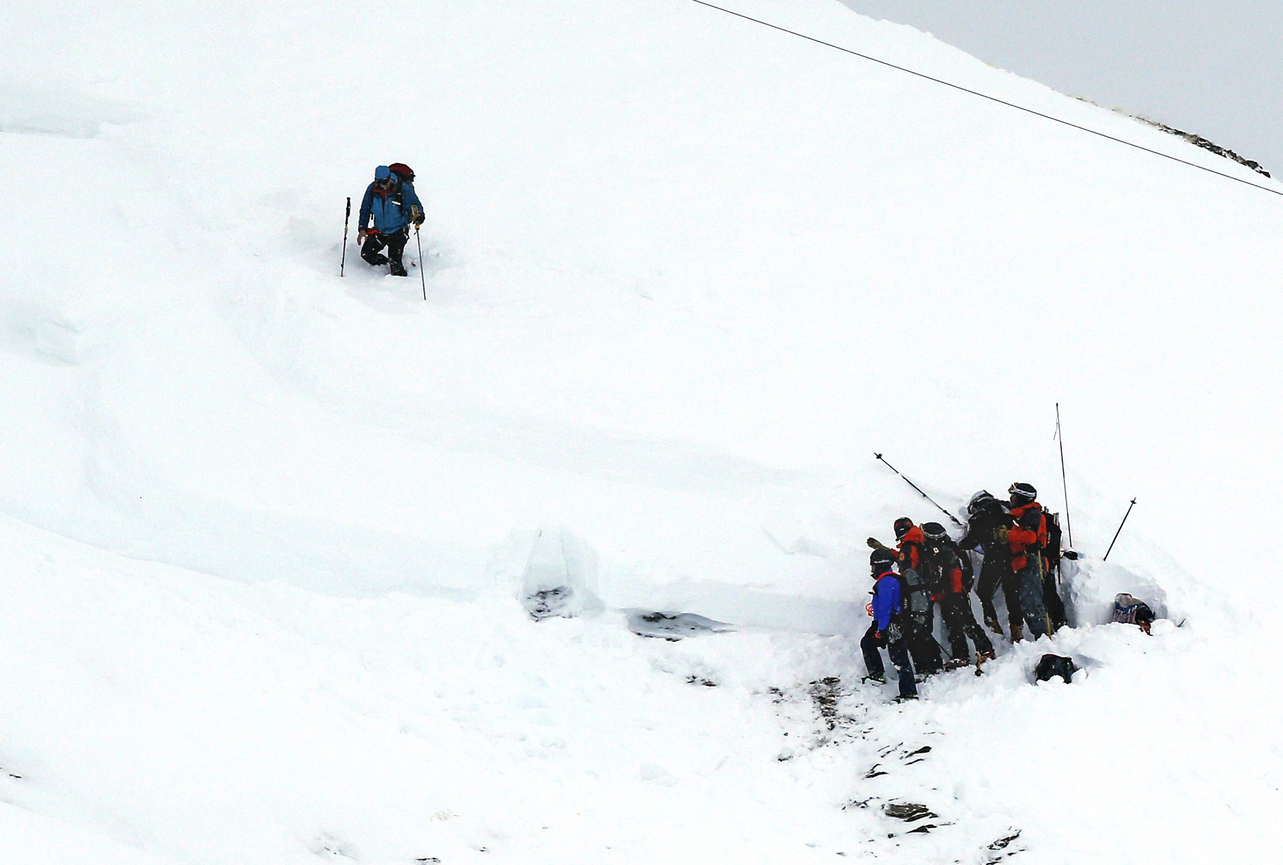 Members of a rescue team search in the snow for missing people after an avalanche swept away a group of people that included a party of schoolchildren, in Les Deux Alpes, France on Jan. 14, 2016.