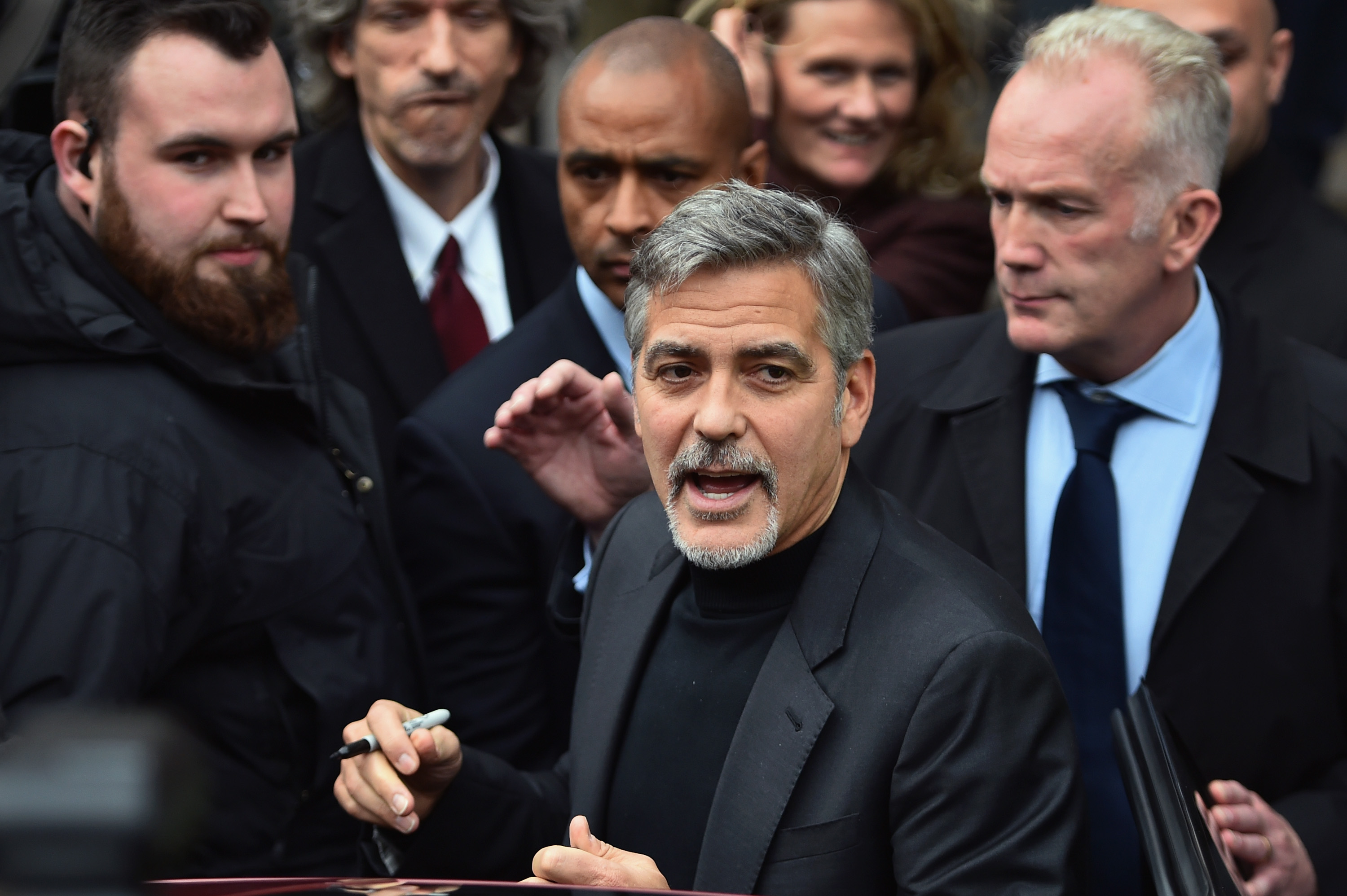 Hollywood actor George Clooney reacts with members of the public as he leaves Tiger Lily restaurant on Nov. 12, 2015 in Edinburgh, Scotland.
