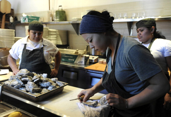 Allie Caran, right, an employee at the Woodberry Kitchen restaurant, shucks an oyster, April 2, 2010, in Baltimore, Maryland.  (Photo by Lloyd Fox/Baltimore Sun/MCT via Getty Images)