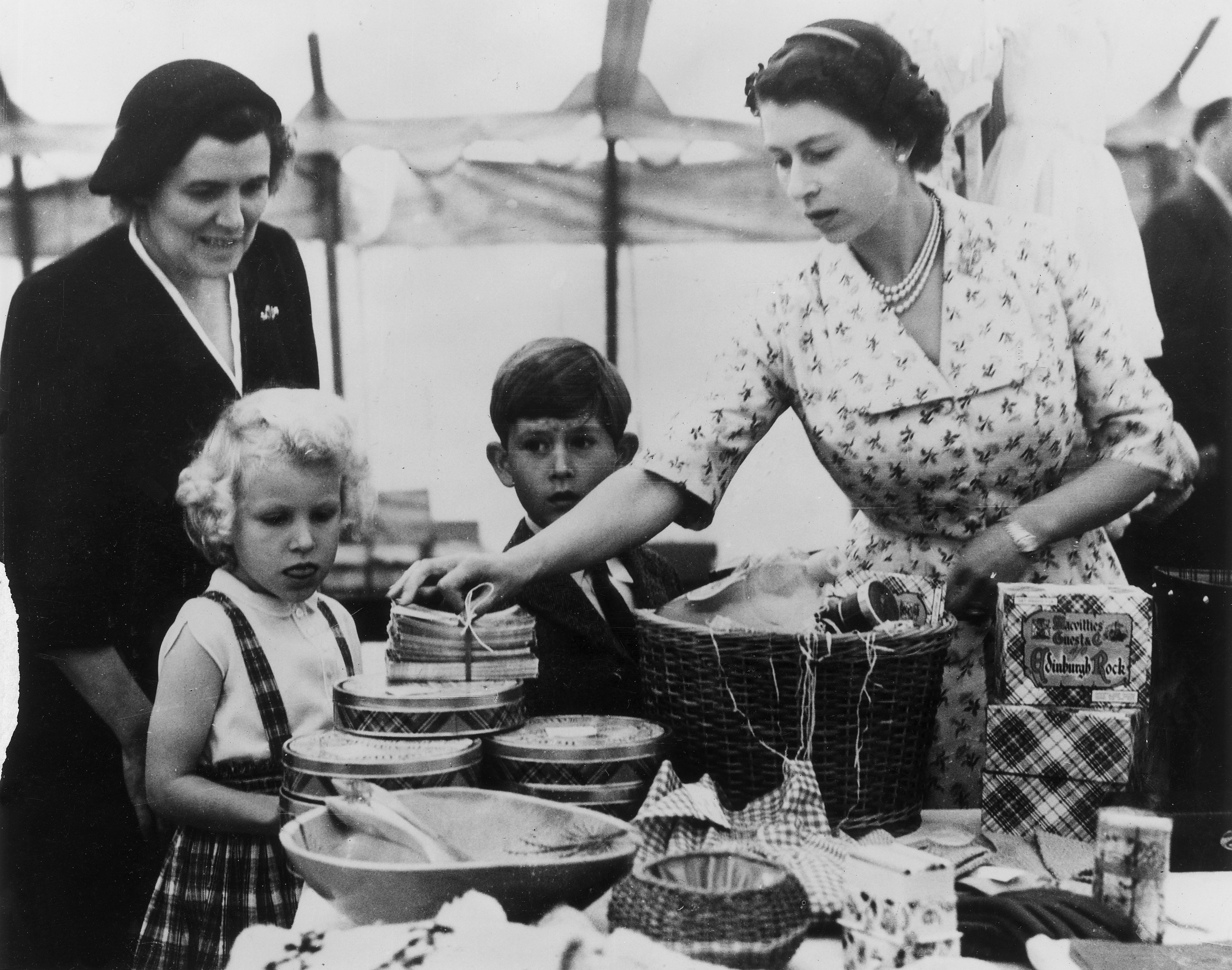 Queen Elizabeth II with Princess Anne, and Prince Charles at a stall during a Sale of Work event in Abergeldie Castle, near Balmoral Castle in Aberdeenshire, on August 22, 1955, to raise funds for the building of a new vestry at Craithie Church.