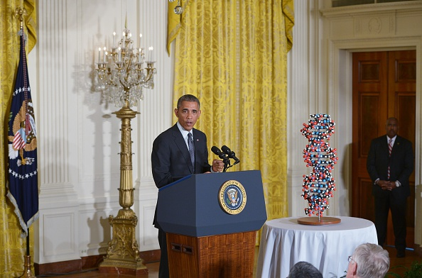 US President Barack Obama speaks on investments in  precision medicine  on January 30, 2015 in the East Room of the White House in Washington, DC. At right is a 17-base pair DNA model. President Obama on Friday unveiled plans to plow $215 million into  precision medicine  research, a field he said provided  boundless' promise for the treatment of diseases like cancer and diabetes. AFP PHOTO/MANDEL NGAN        (Photo credit should read MANDEL NGAN/AFP/Getty Images)