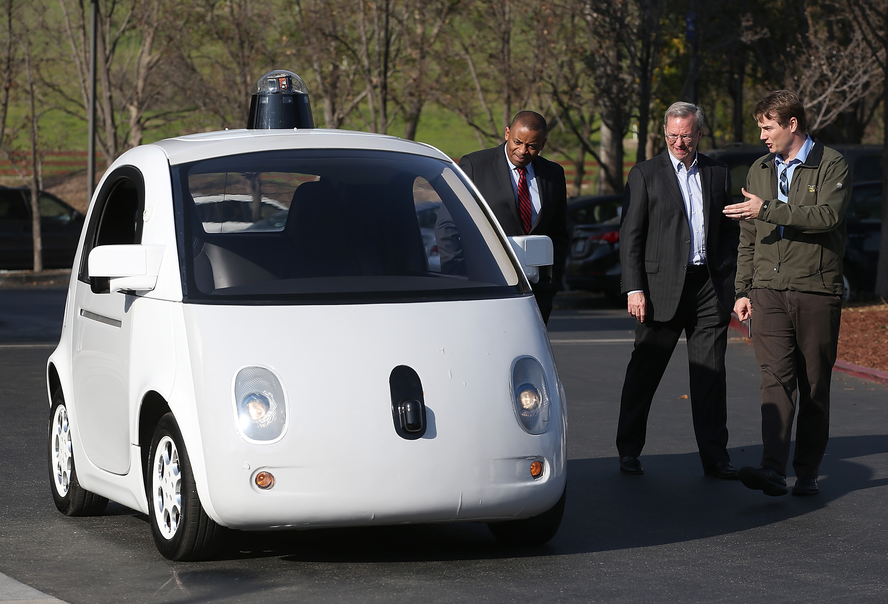 Google's Chris Urmson (R) shows a Google self-driving car to U.S. Transportation Secretary Anthony Foxx (L) and Google Chairman Eric Schmidt (C) at the Google headquarters on February 2, 2015 in Mountain View, California.