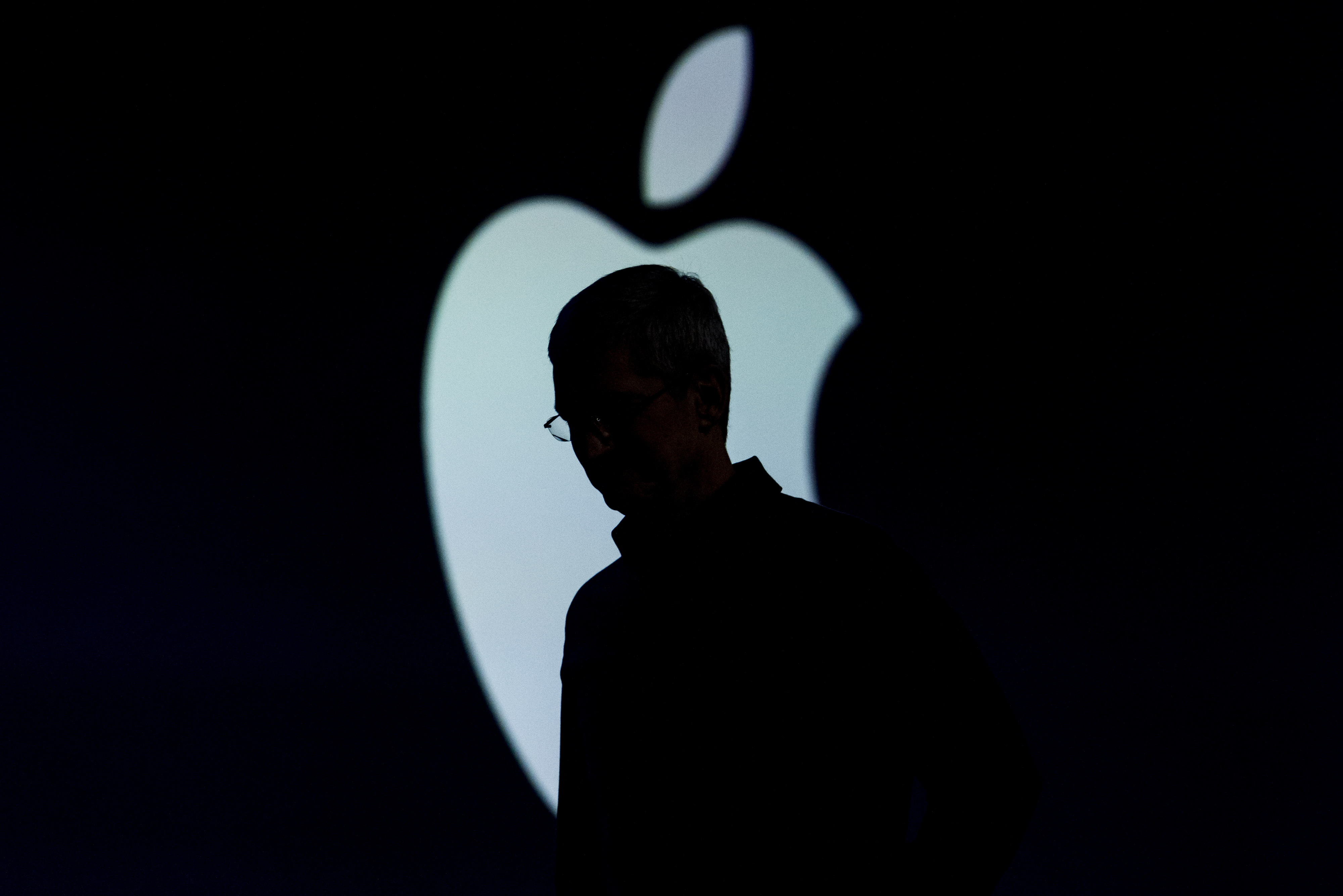 The silhouette of Tim Cook, chief executive officer of Apple Inc., is seen as he exits the stage during the Apple World Wide Developers Conference (WWDC) in San Francisco, California, U.S., on Monday, June 8, 2015.