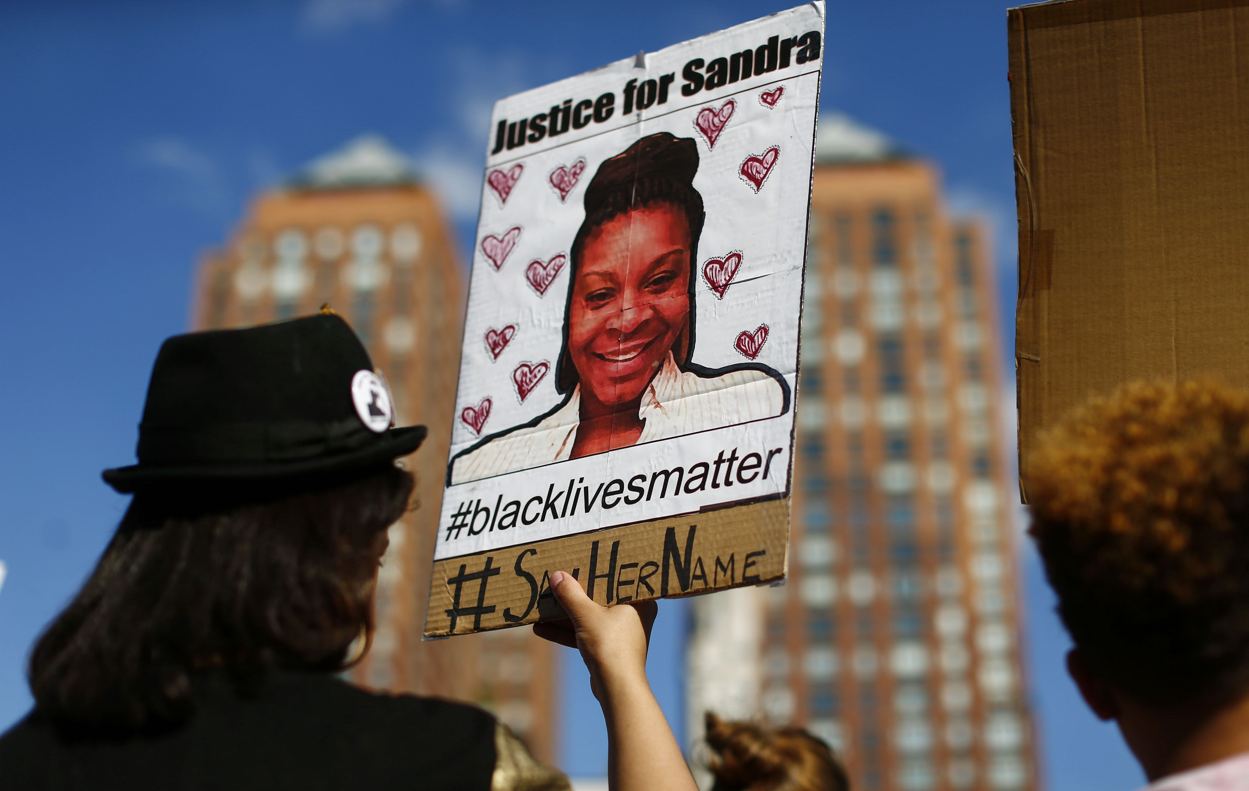 A woman holds a poster bearing the portrait of  Sandra Bland, a 28-year-old black woman who killed herself in a Texas jail cell on July 13th, during a Michael Brown memorial rally in Union Square in New York on Aug. 9, 2015.