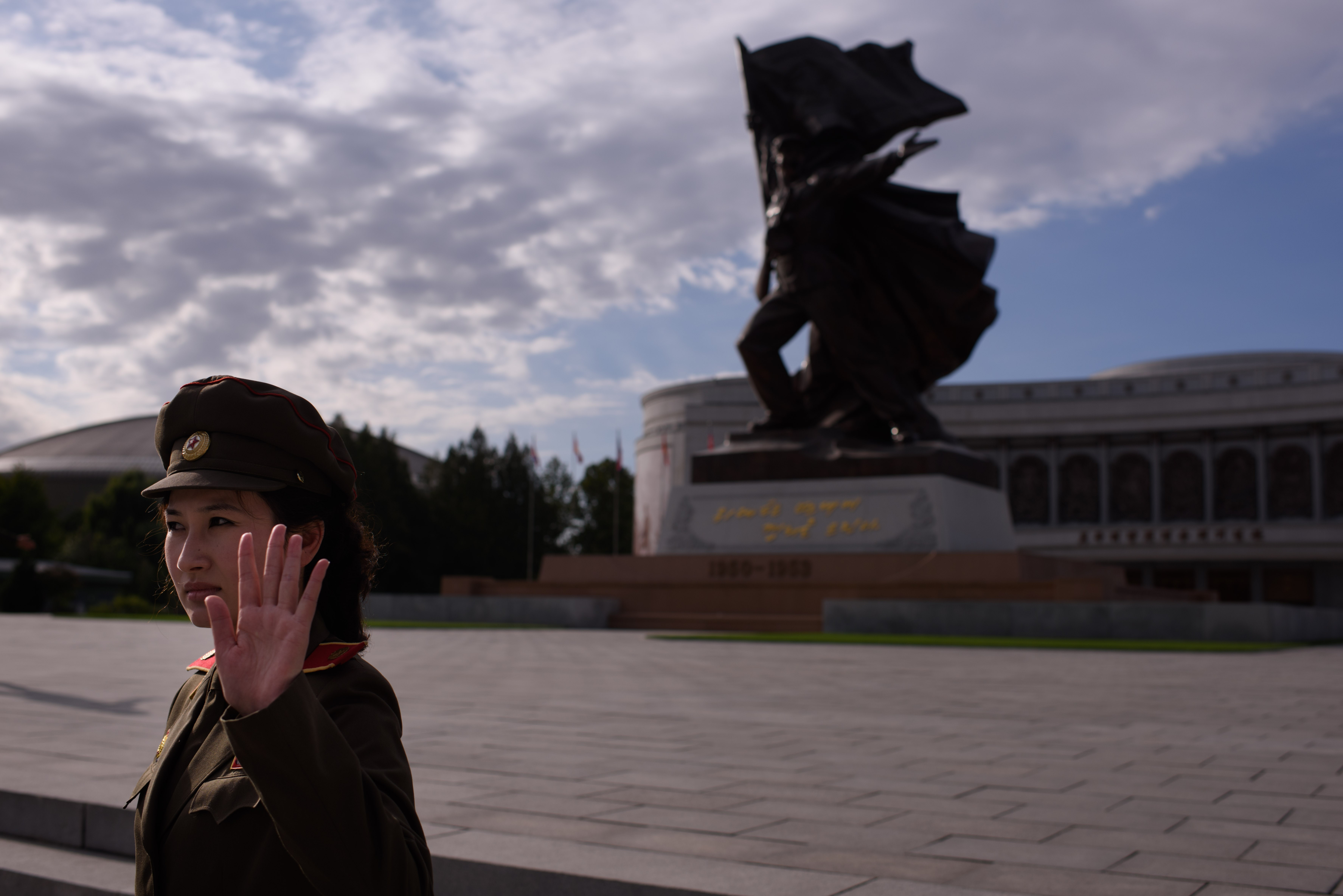 A uniformed tour guide gestures to tourists outside the War Museum in Pyongyang on Oct. 9, 2015