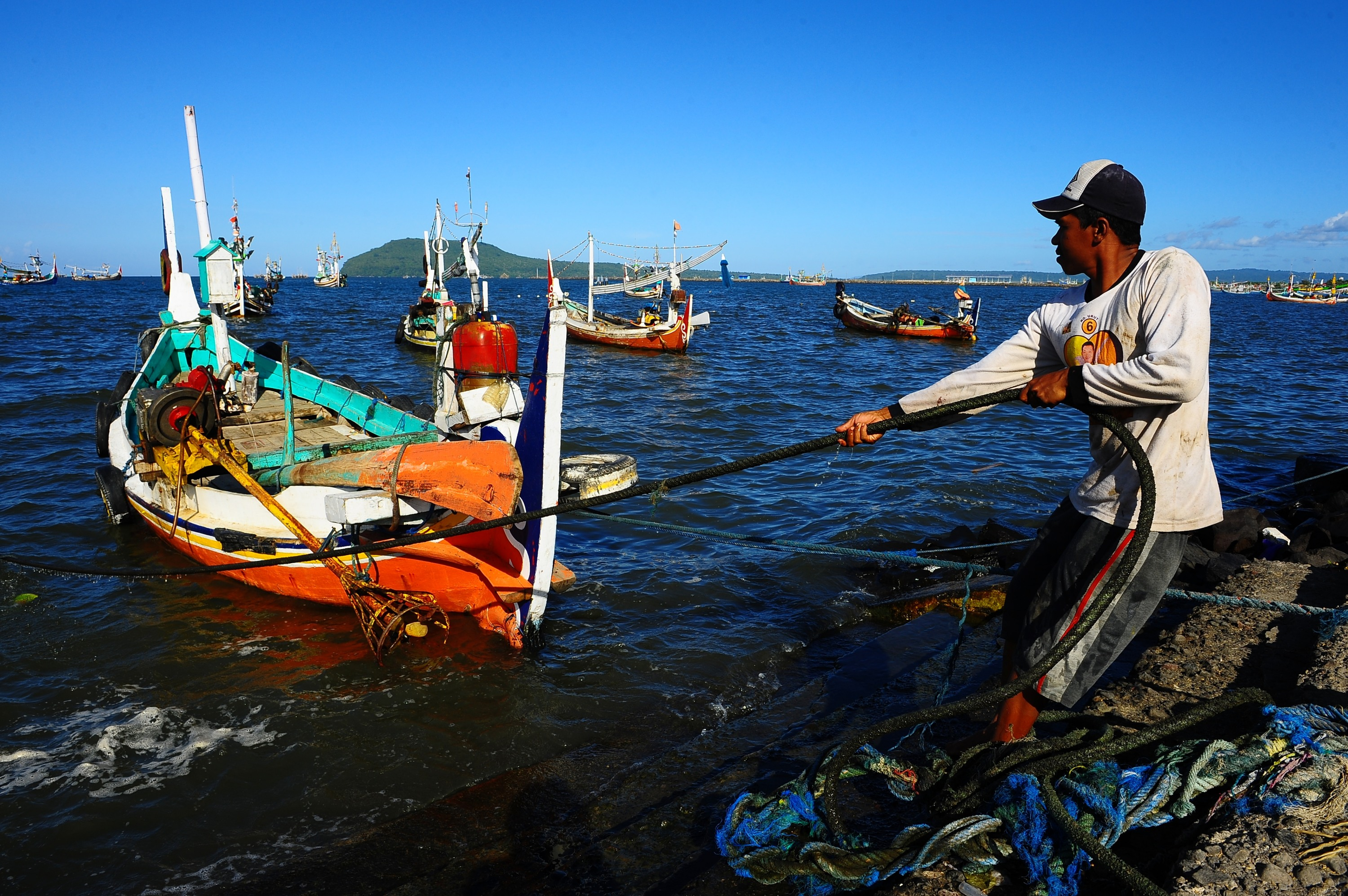 An Indonesian fisherman pulls the boat docked at Muncar Port on May 25, 2014, in Banyuwangi, Indonesia. Indonesia has become one of the major exporters of meat and shark fins in the world