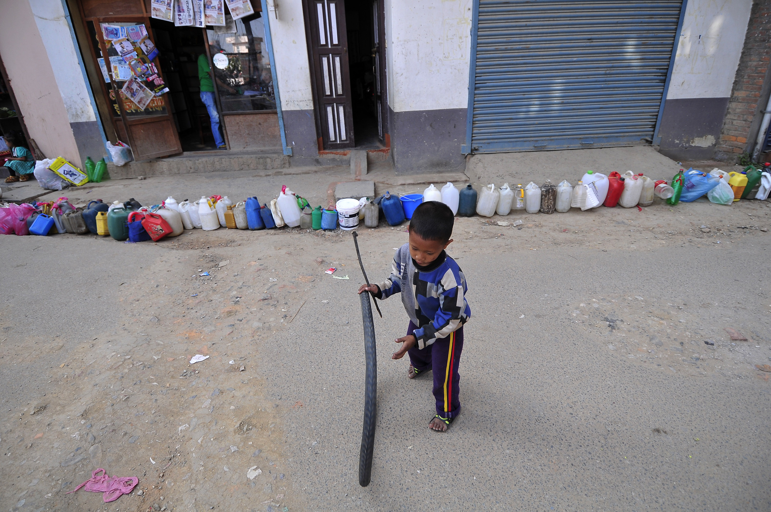 A Nepalese child plays while waiting for his parents' time to buy kerosene. Protests at the border with India have blocked the transportation of fuel and daily commodities to Nepal.