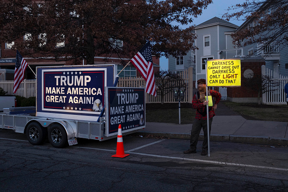 A protester stands beside a pro-Trump billboard outside the Sheraton Portsmouth Harborside Hotel where Republican Presidential candidate Donald Trump is due to speak at the New England Police Benevolent Association Meeting December 10, 2015 in Portsmouth, New Hampshire.