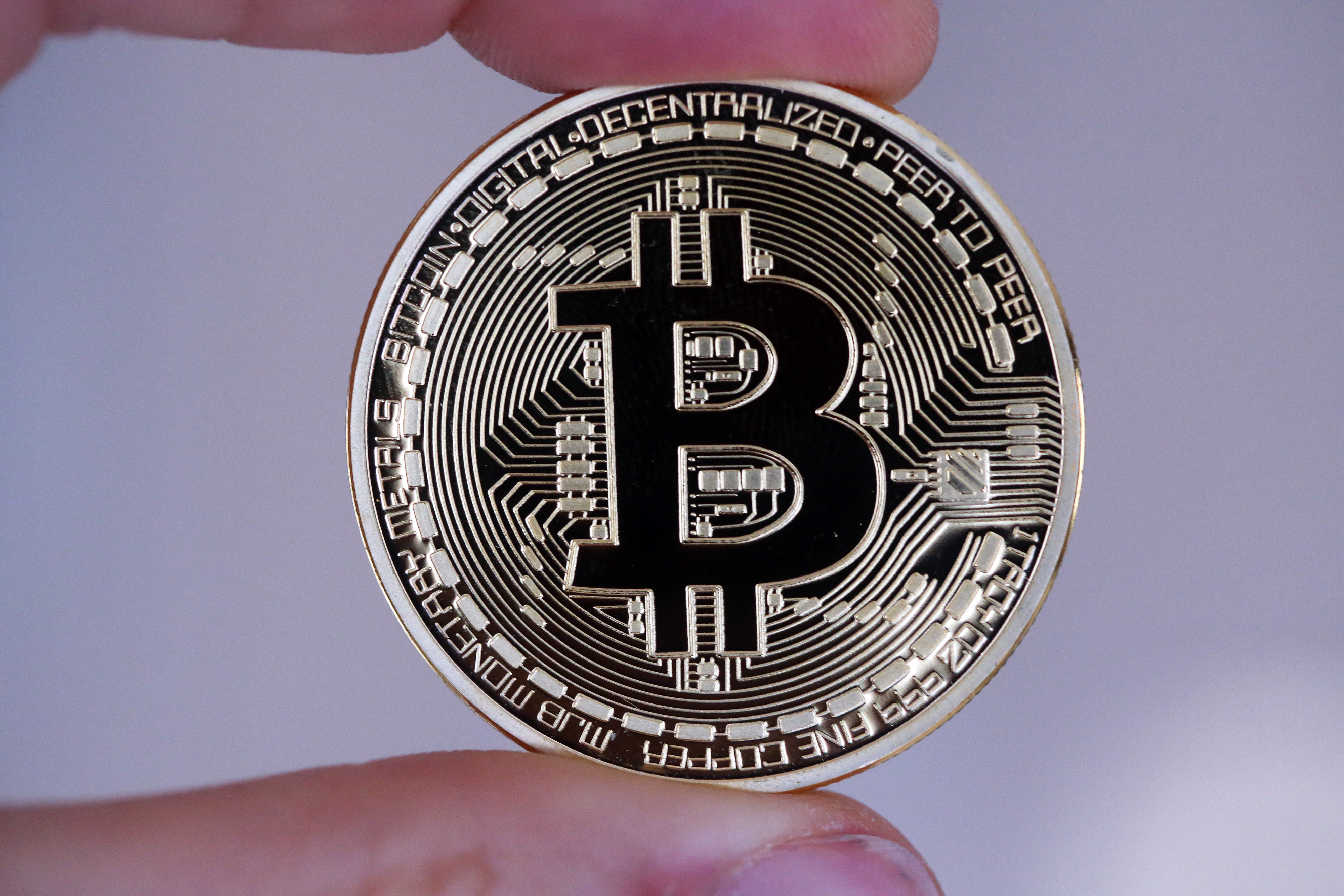 A Bitcoin is held for an arranged photograph in Danbury, U.K., on Dec. 10, 2015.