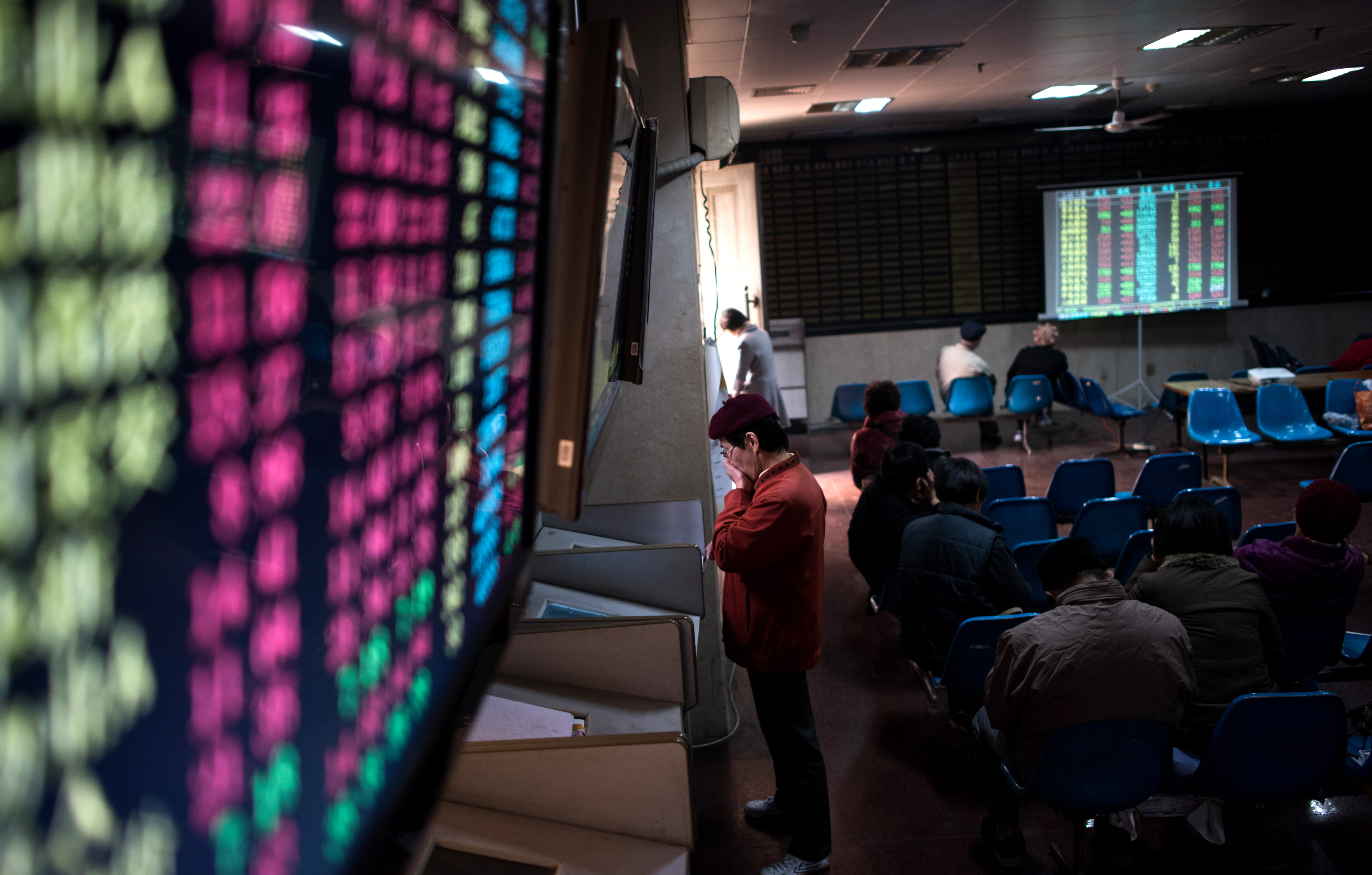 In this photo taken on December 15, 2015, an investor monitors screens showing stock market movements at a brokerage house in Shanghai.