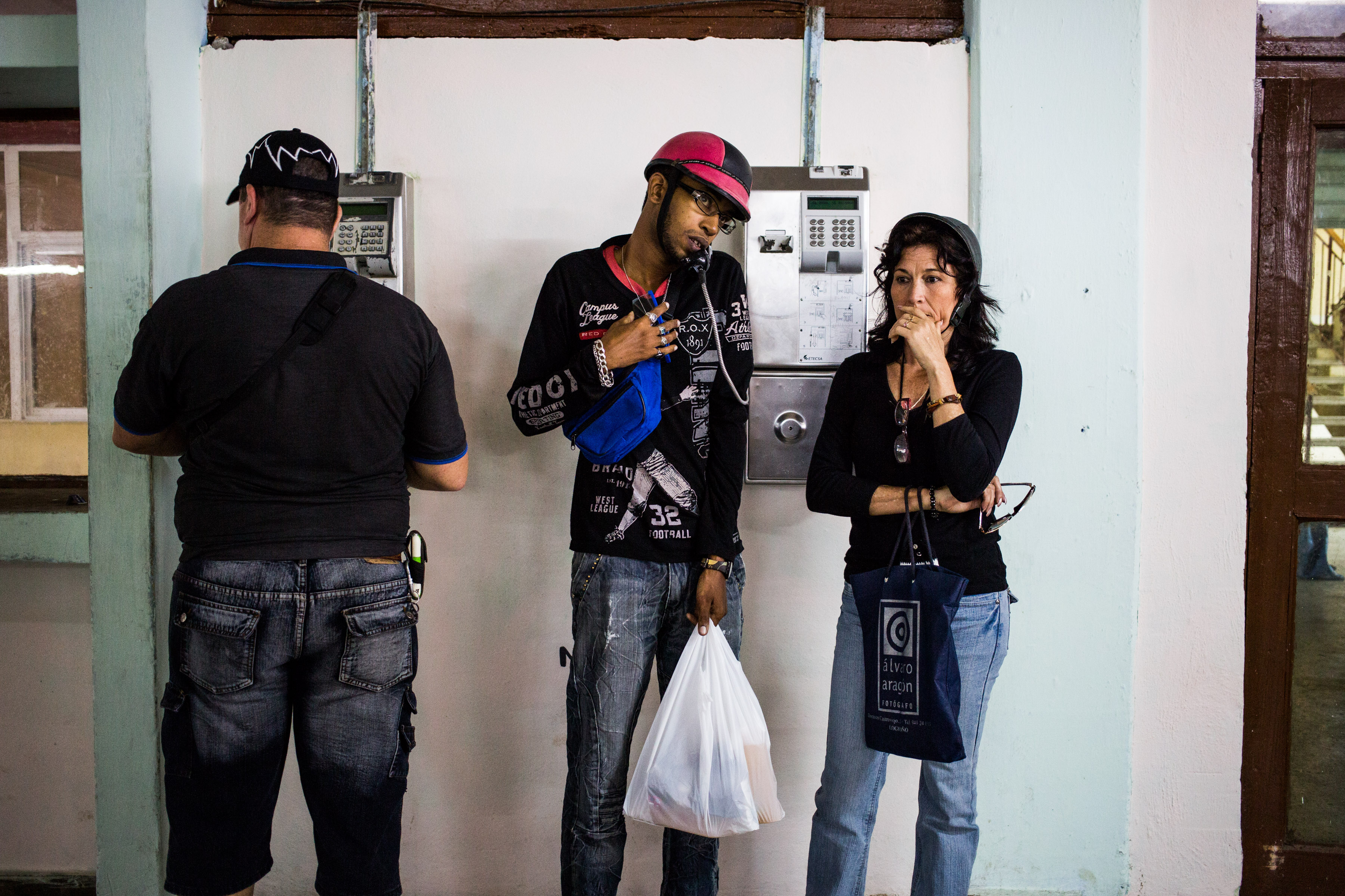 ALAMAR, CUBA - DECEMBER 19 - Alberto Garcia Rivera (center) talks on a payphone at the Falcon shopping center, Alamar.
