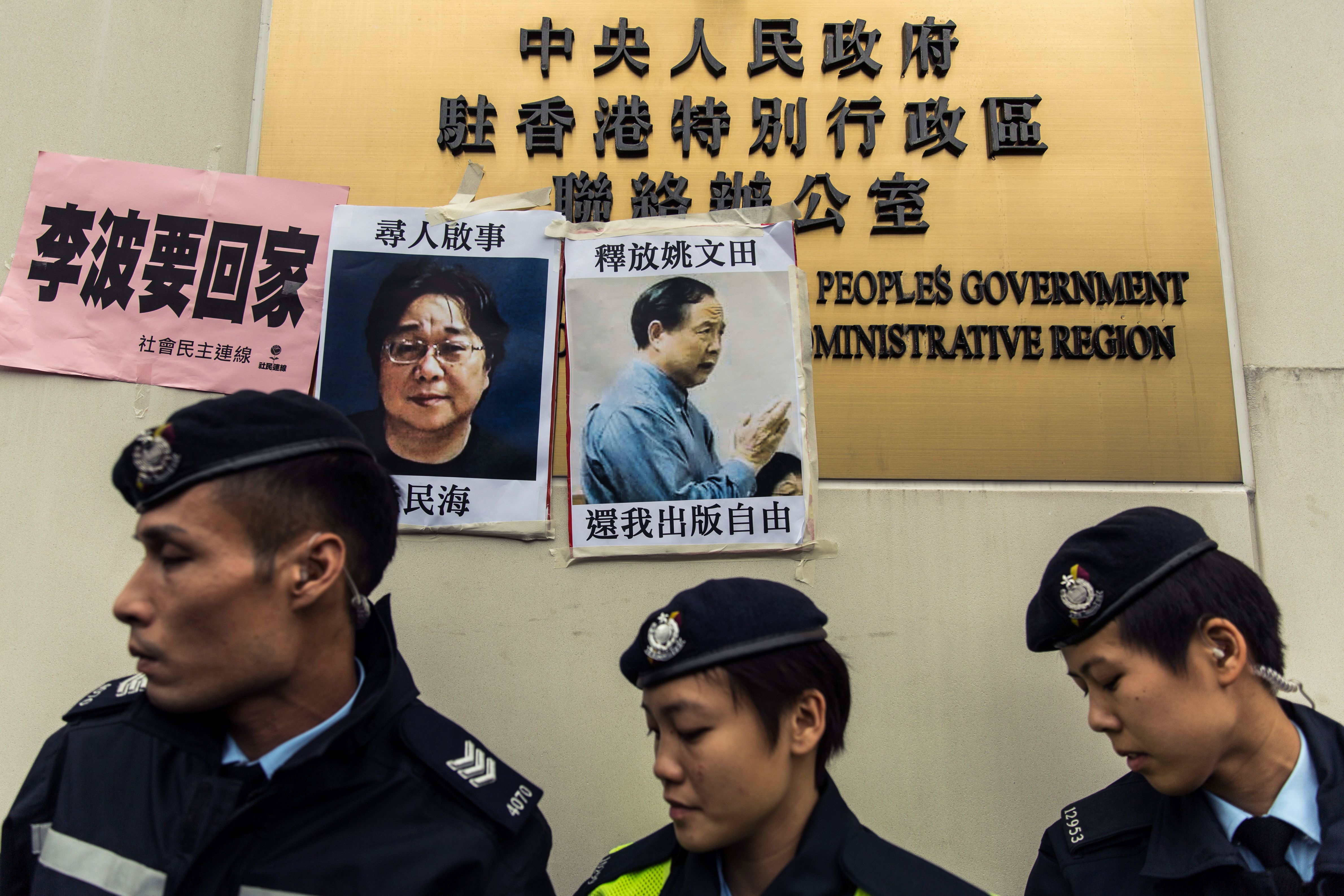 Police walk past missing-person notices for Gui Minhai, left, among five missing booksellers from the Mighty Current publishing house, and Yau Wentian, a Hong Kong publisher who was jailed for 10 years in 2015 while preparing to release a book critical of Chinese President Xi Jinping, posted on top of the sign of China's Liaison Office in Hong Kong on Jan. 3, 2016.