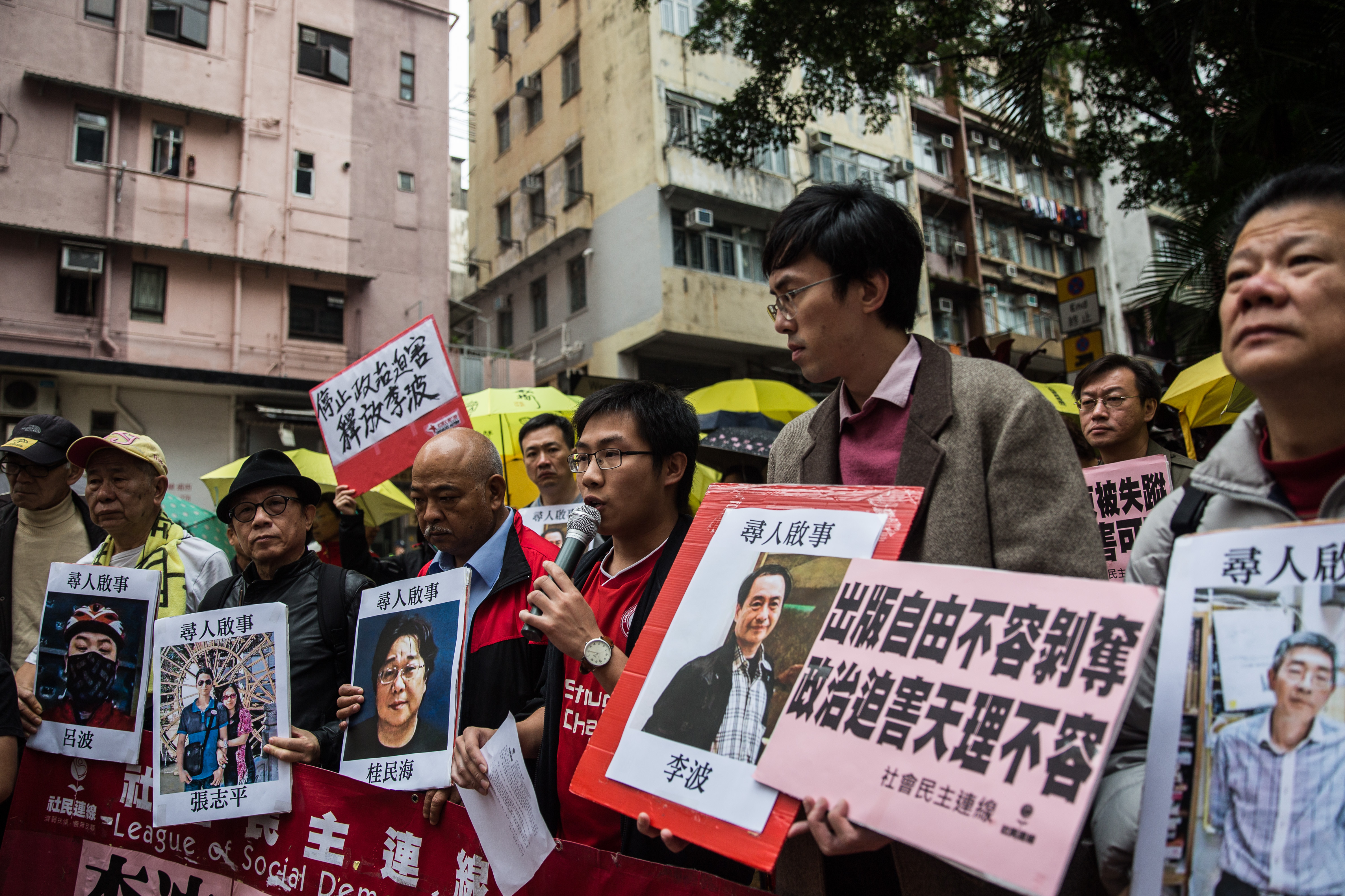 Protesters hold up images of missing publishers of books critical of China, including the latest to vanish, Lee Bo, as they walk toward China's Liaison Office in Hong Kong on Jan, 3, 2016