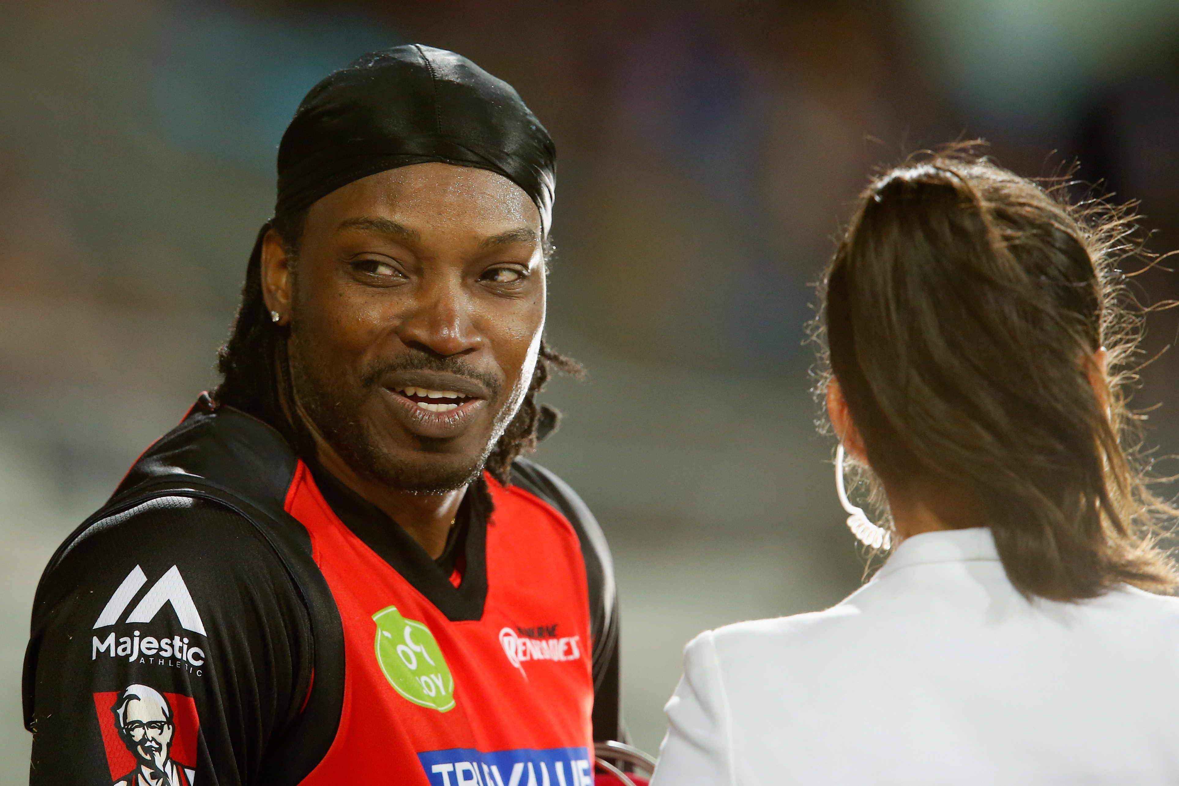 Chris Gayle of the Melbourne Renegades gives a TV interview to Mel Mclaughlin during the Big Bash League match between the Hobart Hurricanes and the Melbourne Renegades at Blundstone Arena in Hobart, Australia, on Jan. 4, 2016