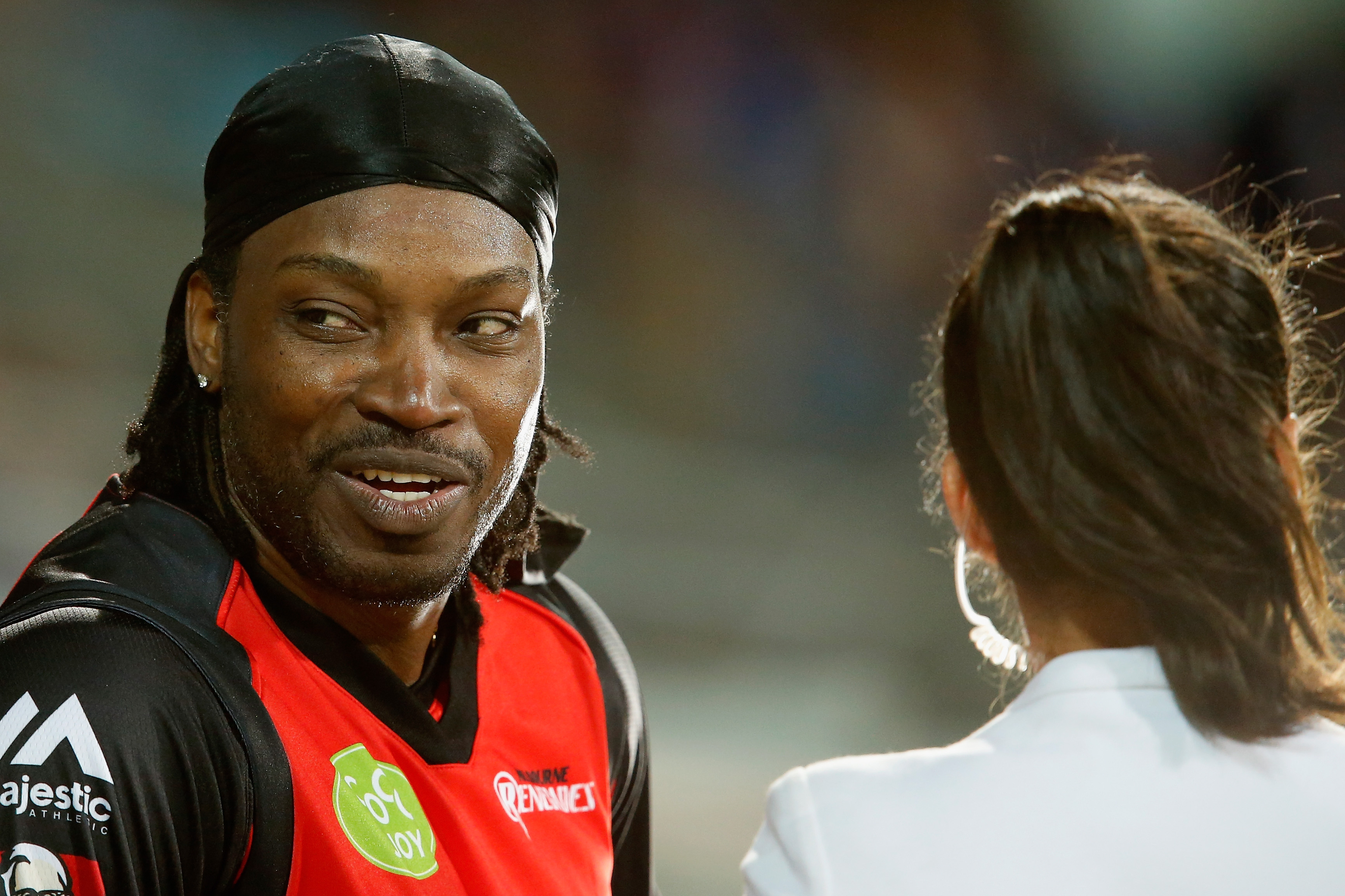 Chris Gayle of the Melbourne Renegades gives a TV interview to Mel Mclaughlin during the Big Bash League match at Blundstone Arena on Jan. 4, 2016, in Hobart, Australia