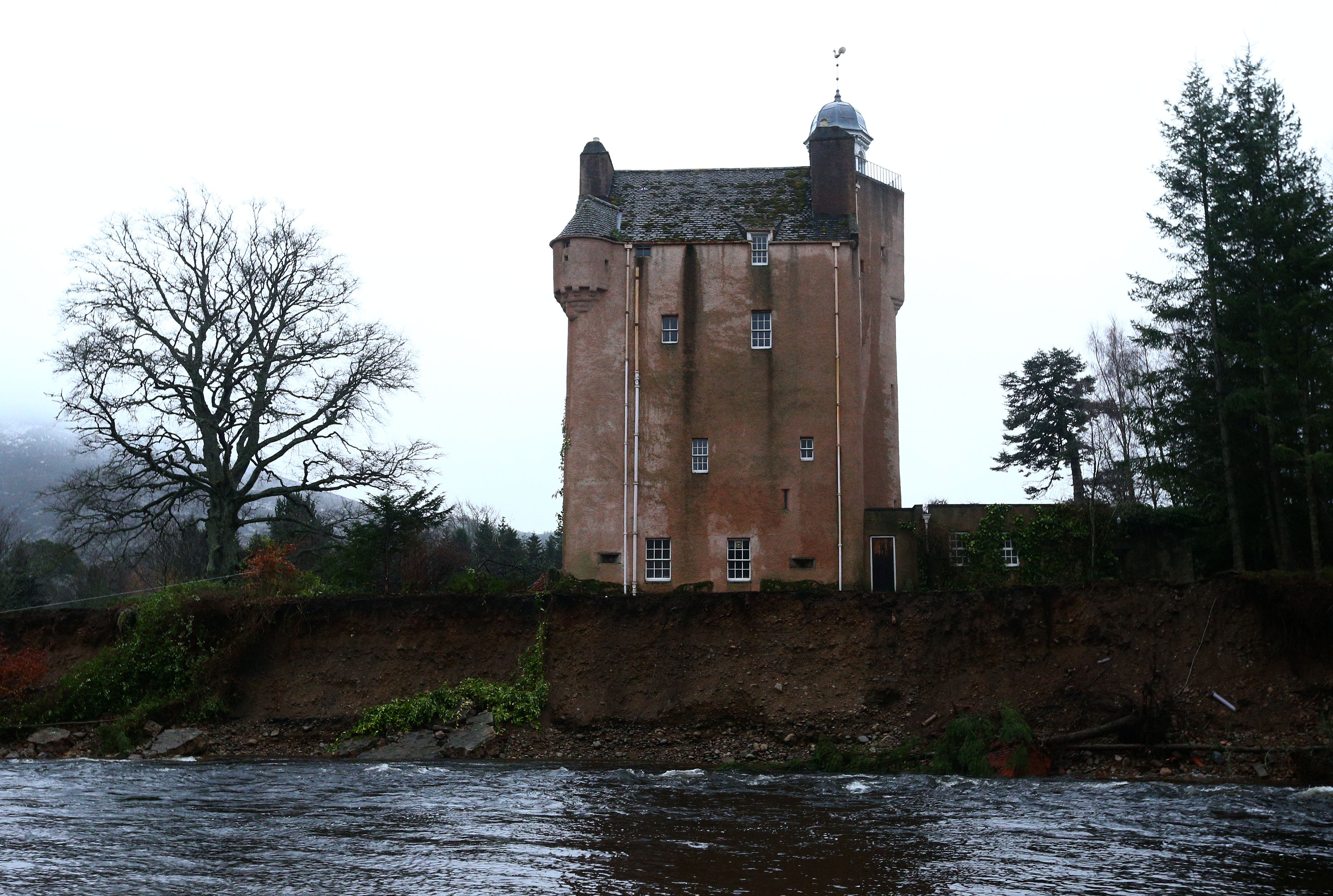 BALLATER, SCOTLAND - JANUARY 5 : 450 year old Abergeldie Castle owned by John Seton Howard Gordon, the Baron of Abergeldie, sits precariously on the edge of the River Dee after storm surge swept away the river bank on January 5, 2016 in Ballater, United Kingdom. Storm Gertrude is the latest winter storm to bring heavy rain fall and flooding to the north of England and Scotland, causing widespread disruption to transport and infrastructure. (Photo by Mark Runnacles/Getty Images)