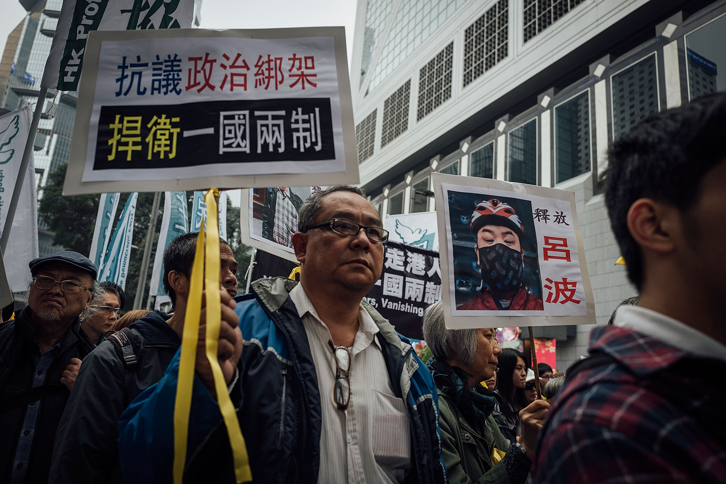 People hold placards and shout slogans as they take part in a rally on a street on Jan. 10, 2016, in Hong Kong. The disappearance of five Hong Kong booksellers, including U.K. passport holder Lee Bo, has sent shivers through Hong Kong as anxiety grows that Chinese control over the city is tightening