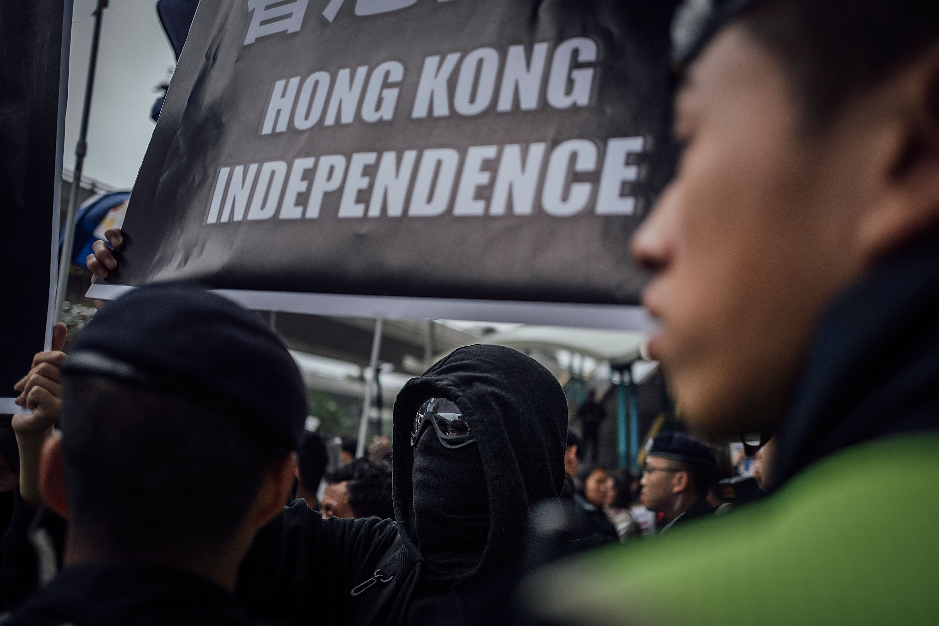 People hold placards and shout slogans as they take part in a rally on a street on Jan. 10, 2016, in Hong Kong over five missing booksellers
