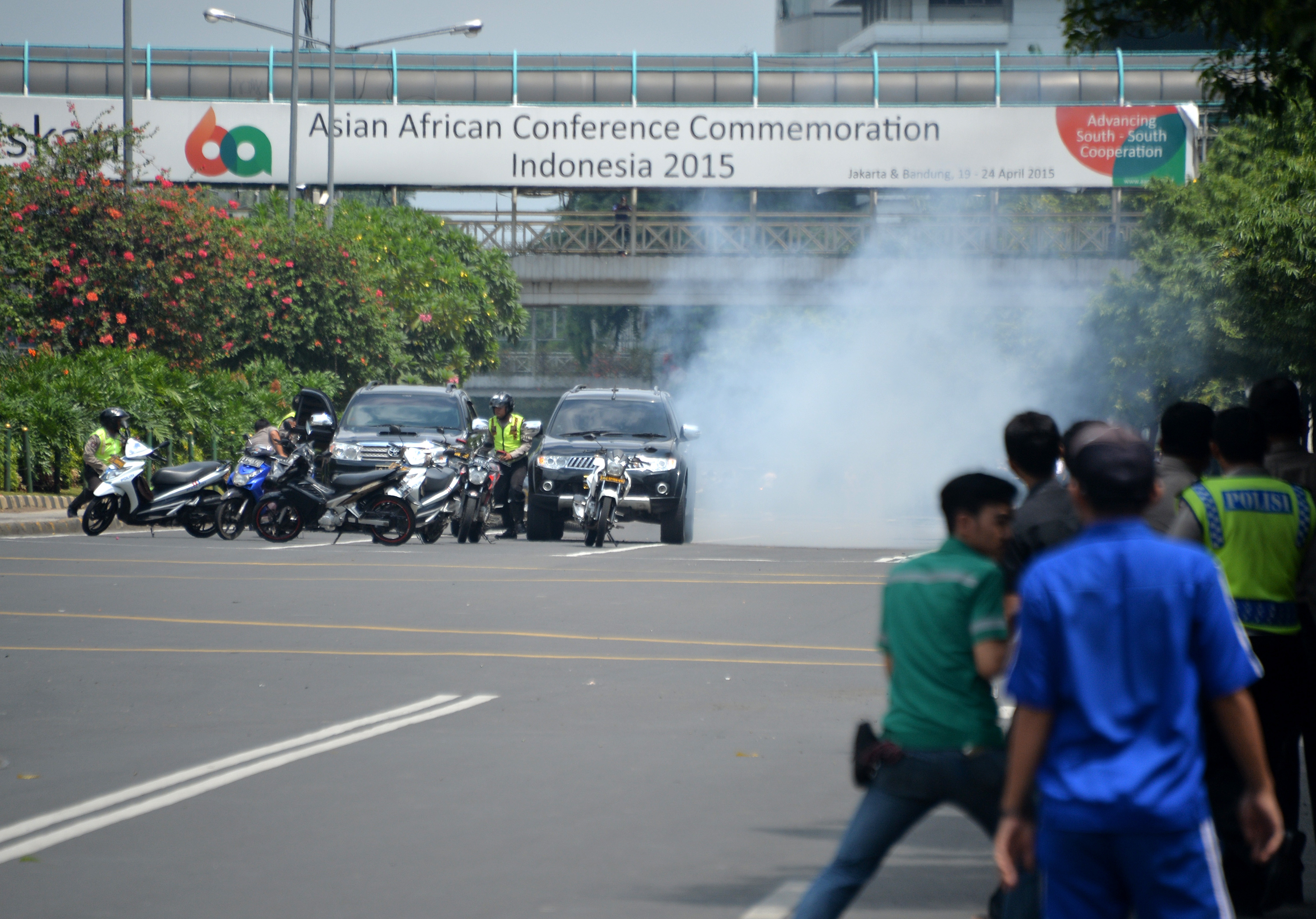 Police hide behind vehicles during an exchange of gunfire with suspects hiding near a Starbucks cafe when another blast happens in Jakarta on Jan. 14, 2016.