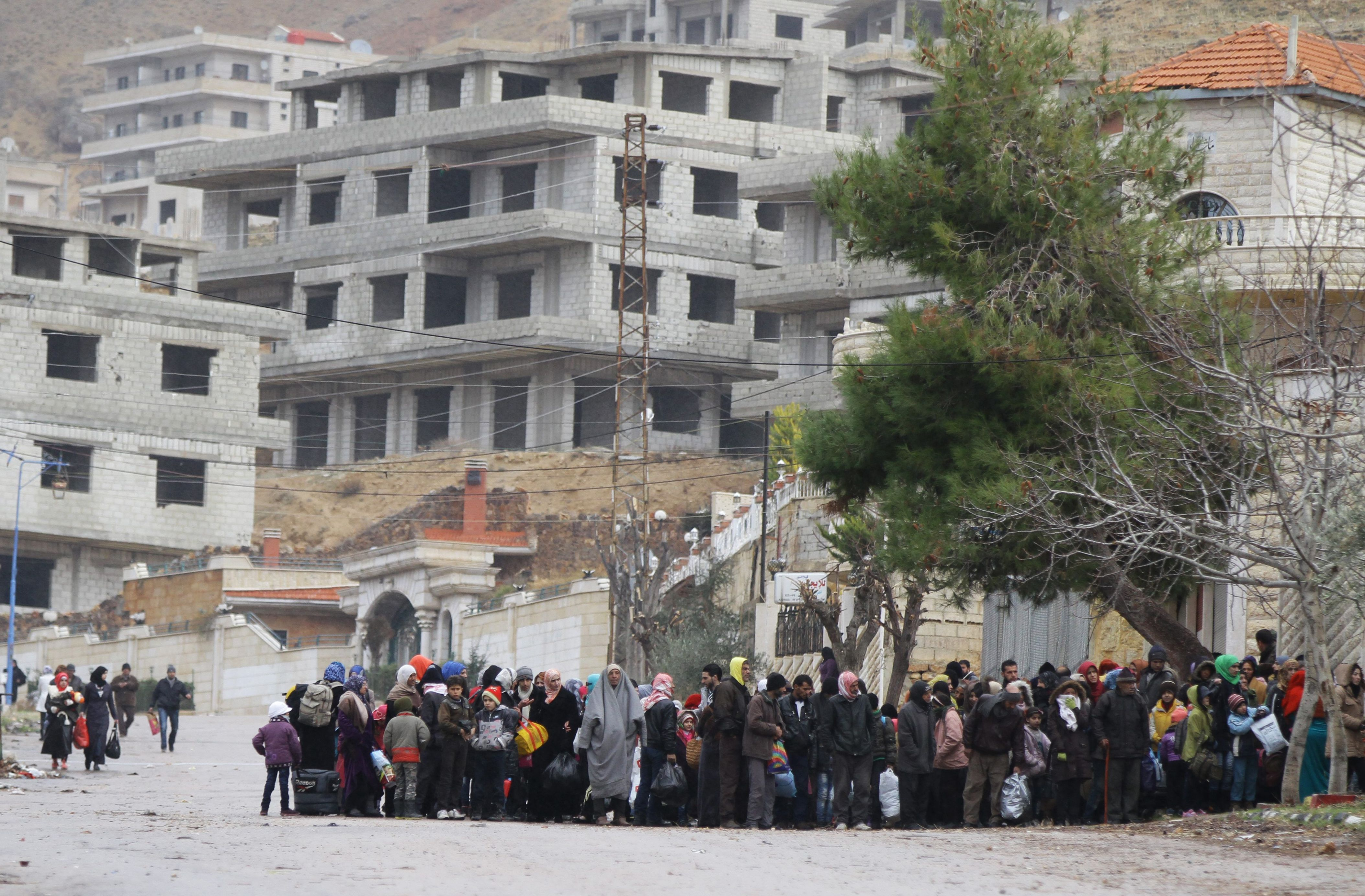 Residents of the besieged rebel-held Syrian town of Madaya wait for a convoy of aid from the Syrian Arab Red Crescent on Jan. 14, 2016