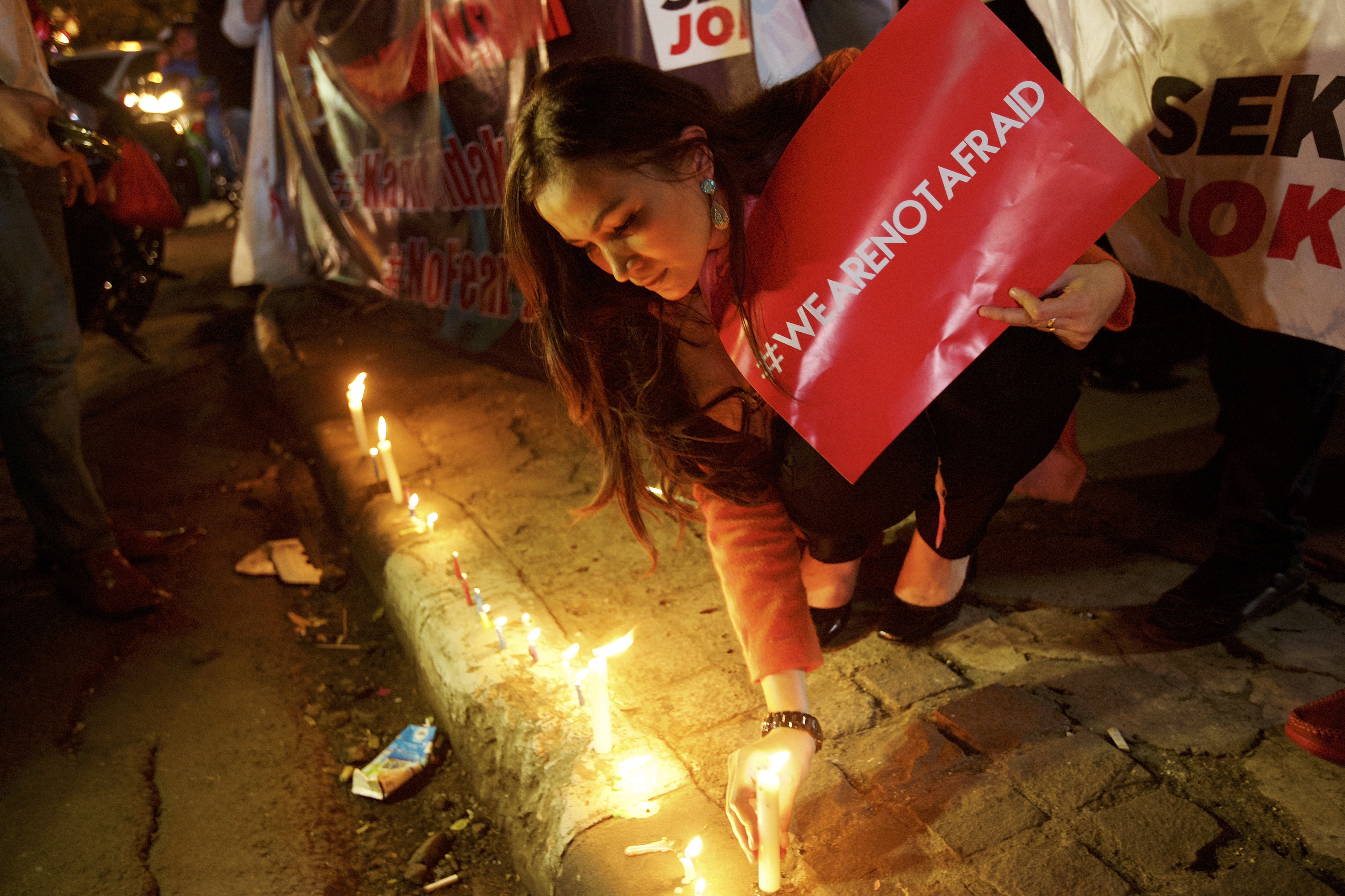 An Indonesian woman lights candles near the site of the terrorist attack during a  We Are Not Afraid  rally on Jan. 15, 2016, in Jakarta
