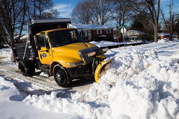 WASHINGTON, USA - JANUARY 25: A snow plow clears huge piles of snow from the neighborhood streets in Rockville, Md., USA on January 25, 2015. The Washington region is still recovering from the massive amounts of snow that fell over the weekend from Winter Storm Jonas with much of the subway system closed and most streets not yet fully cleared. (Photo by Samuel Corum/Anadolu Agency/Getty Images)
