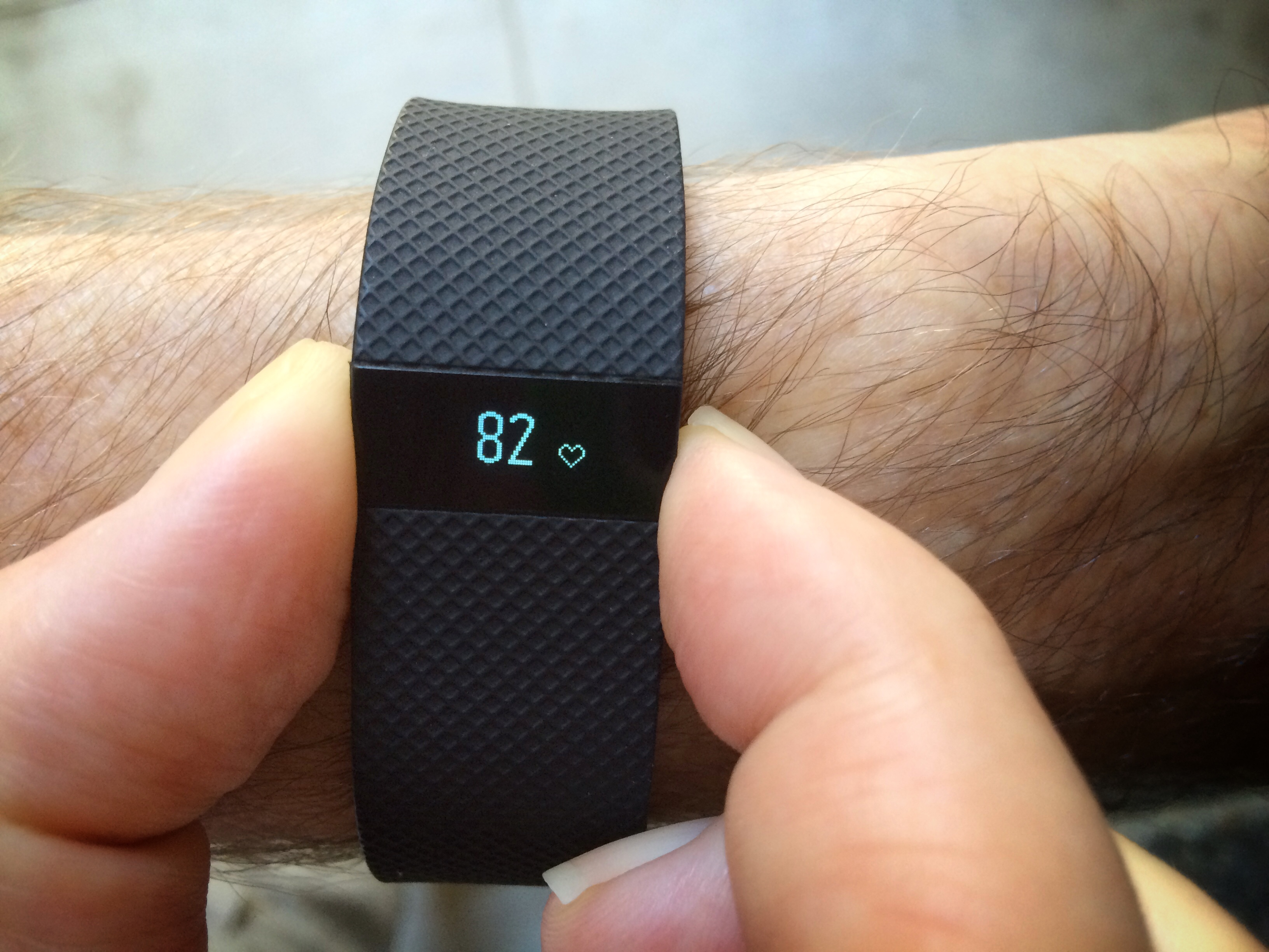 Man checks his heart rate on a FitBit Charge HR wearable activity tracker and monitor