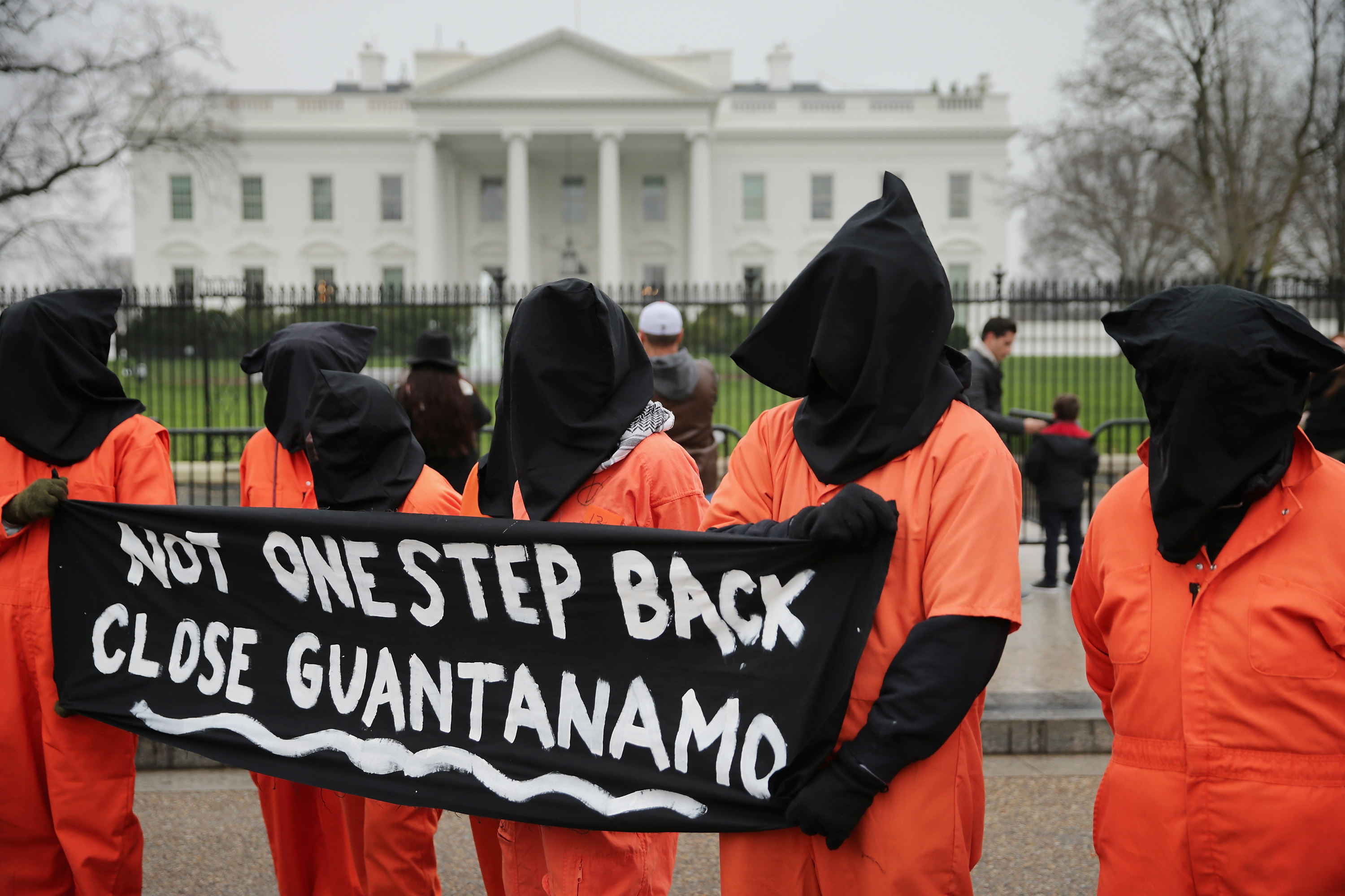Demonstrators with the group Witness Against Torture dress in orange jumpsuits and wear black hoods while demanding that U.S. President Barack Obama close the military prison in Guantanamo, Cuba, outside the White House in Washington, DC.. on Jan. 8, 2016.