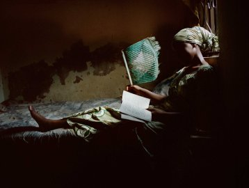Firdausy El-yakub reads a romance novel in her bedroom in Kano, Northern Nigeria, March 21, 2013.