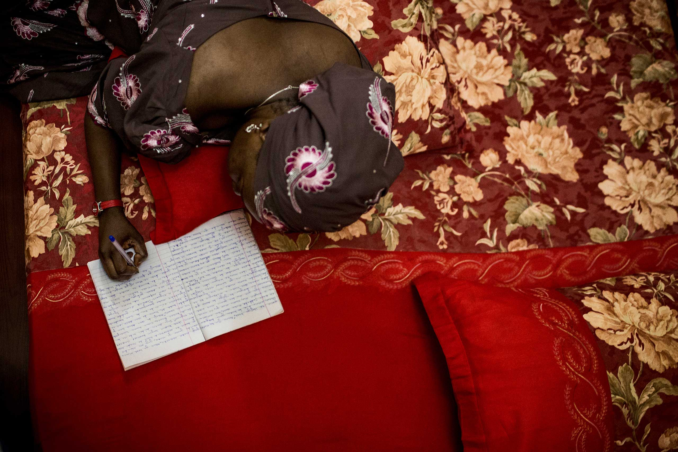 Khadija Gudaji works on her novel while laying in bed at her home in Kano, Northern Nigeria, Sept. 29, 2013.