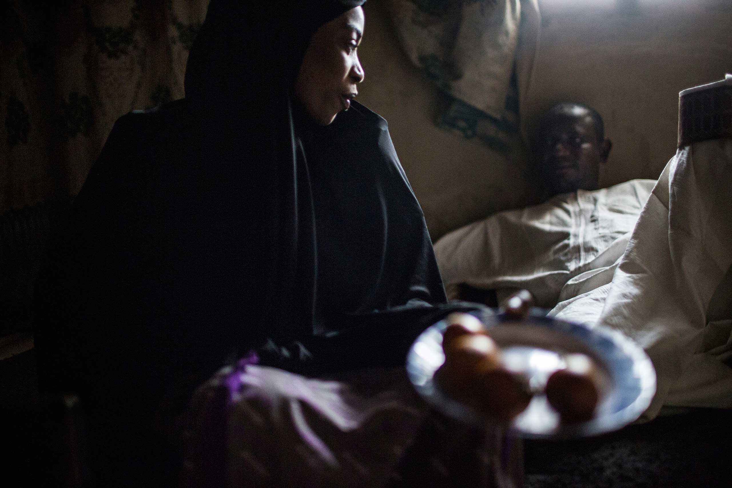 Rabi Tale, a romance novelist, sits at home with one of her suitors, Kano, Northern Nigeria, Feb. 23, 2014.