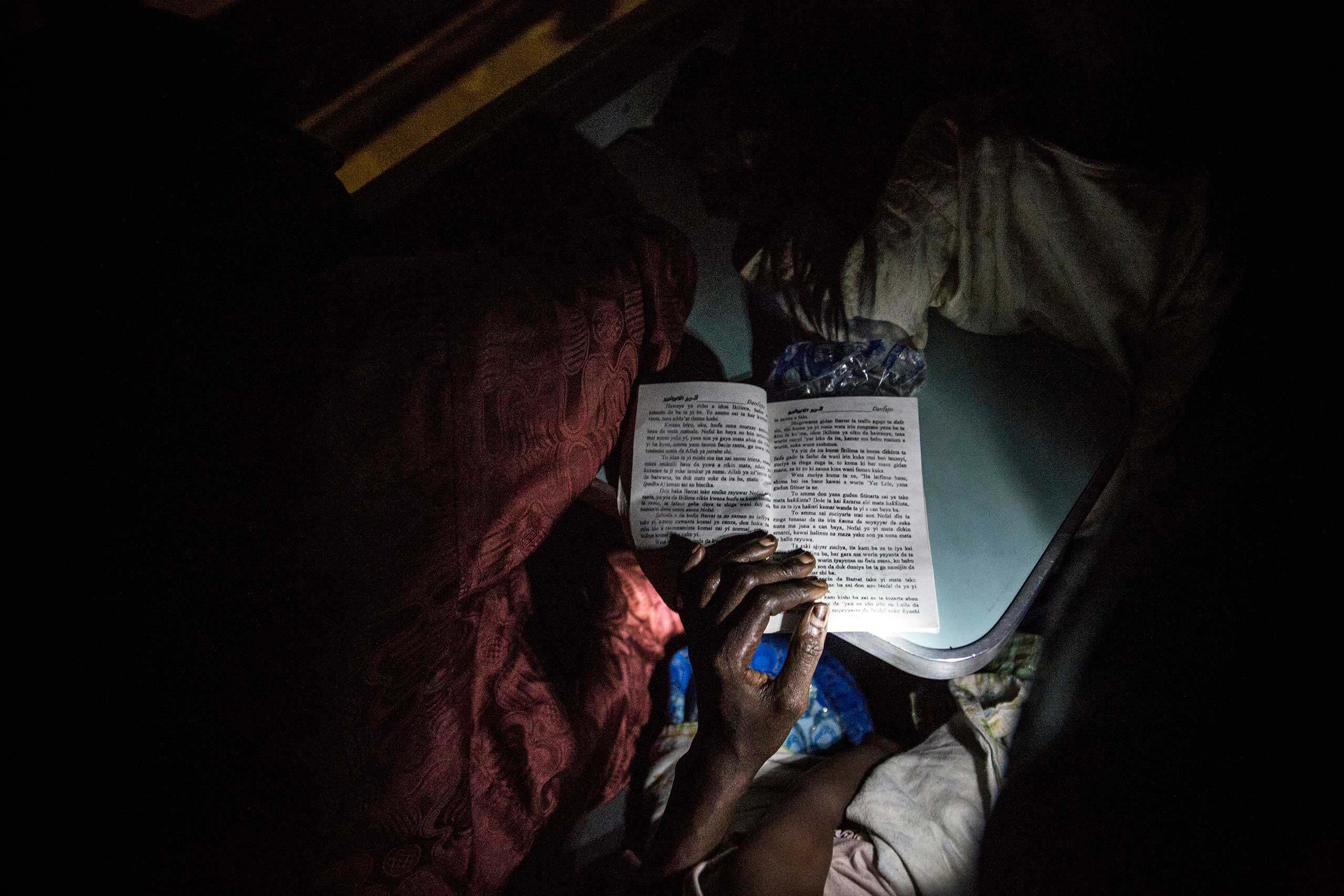 A woman reads a Hausa romance novel using the flashlight on her cell phone while on a train crossing Nigeria, Aug. 21, 2015.