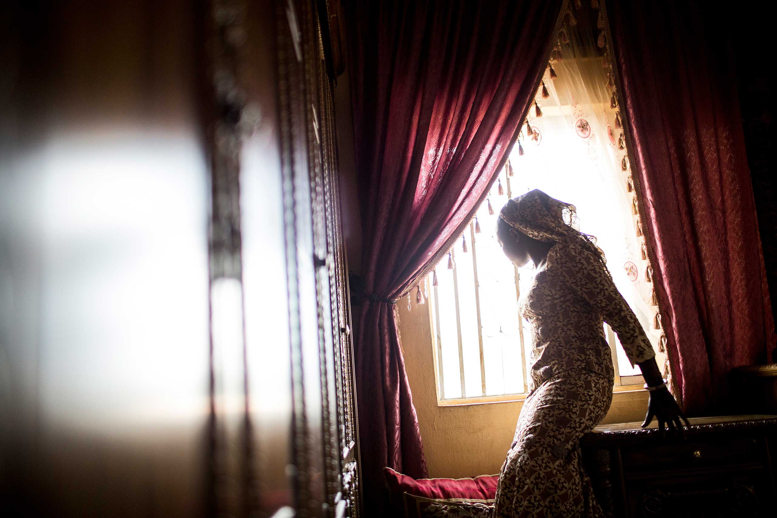 A bride looks out the window before her wedding in Kano, Northern Nigeria, Feb. 28, 2014.