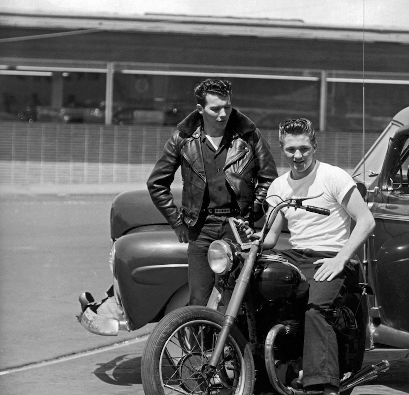 Two youths with ducktail hairdos hanging out with their motorcycle and car. San Francisco, c. 1954
