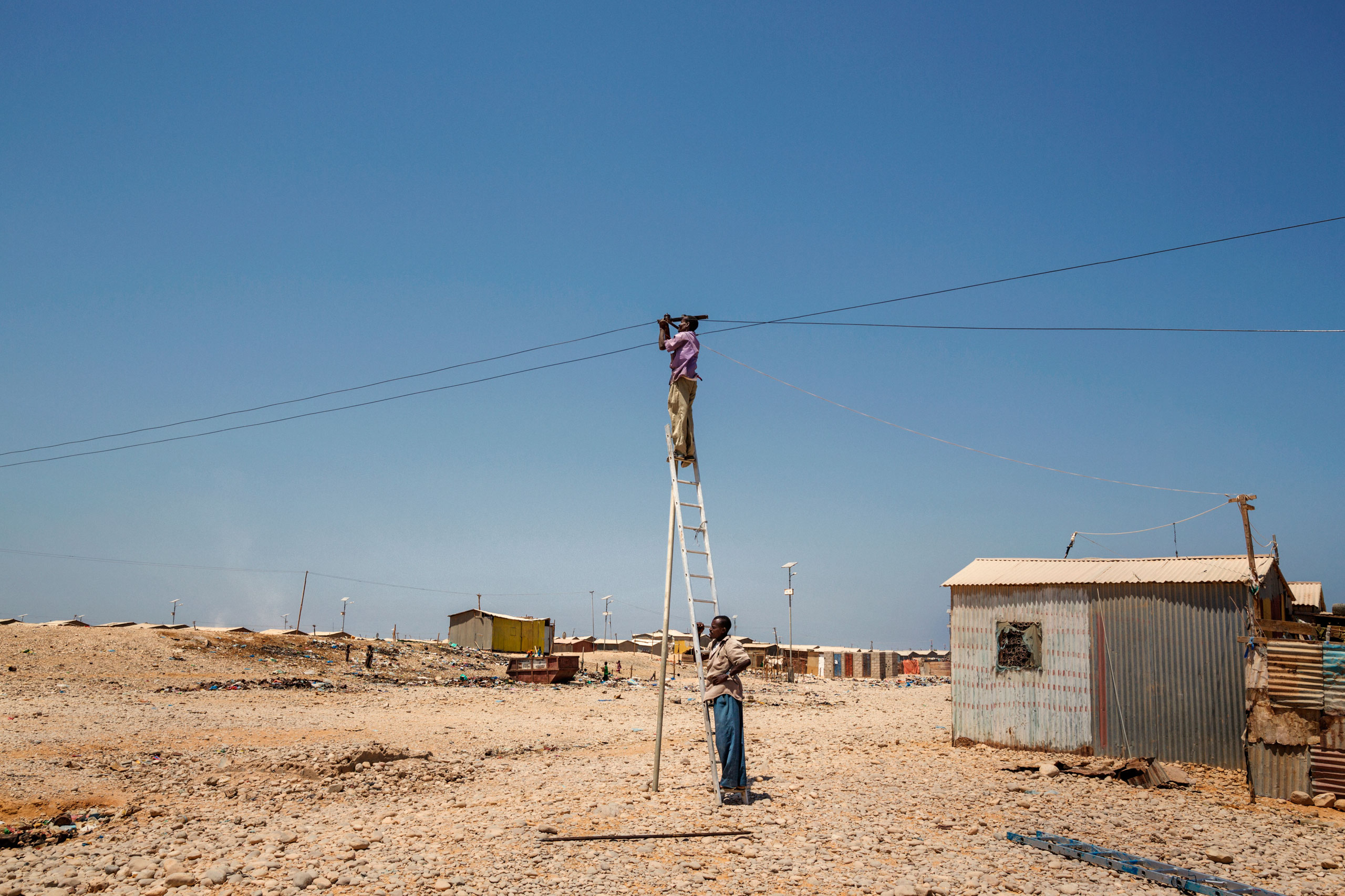 Two men working on a light pole in the Buulo Mingis camp for internally displaced people located in Bosaso, in the north-east region of Somalia. October 5, 2015.