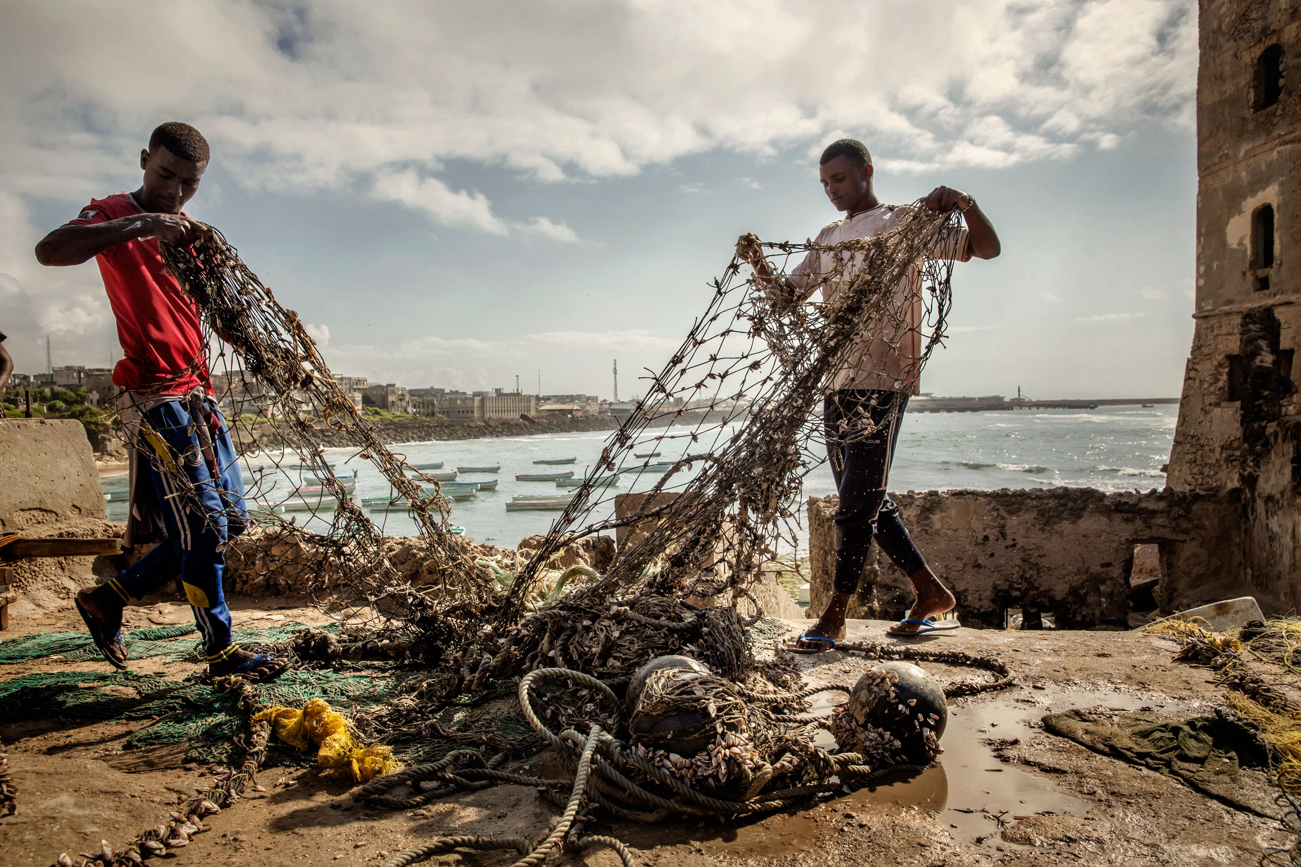 Two sailors repair sails and mend fishing nets. The country's waters have been exploited by illegal fisheries and the economic infrastructure that once provided jobs has been ravaged. Mogadishu, Somalia. October 10, 2015.