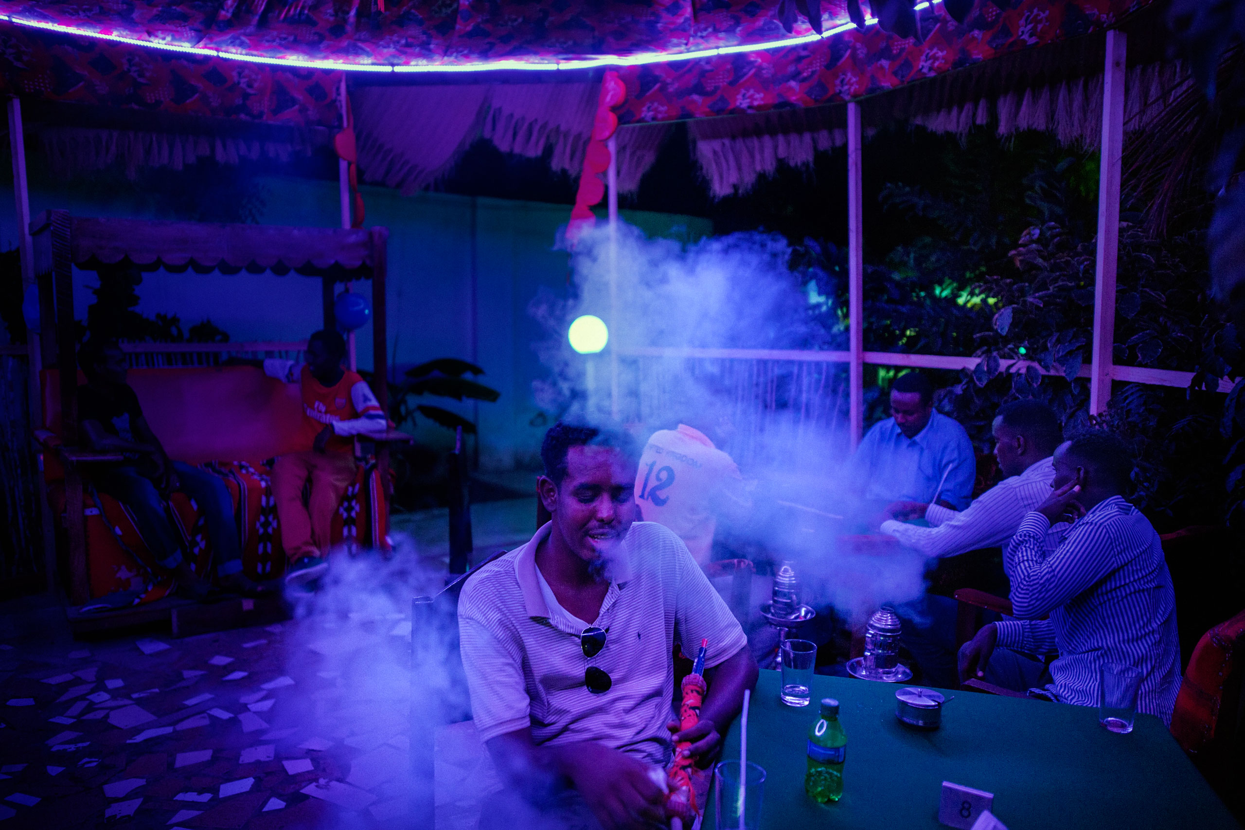 Patrons relax at the Posh Treats, Mogadishu's first country club. Located within a well-protected complex, at Km5, the club opened in January 2015. Manar Moalin, a 33-year-old woman from the Somali diaspora, is the owner.                               The club offers hairdressing services, live music, restaurant and a shisha room, all activities still prohibited in Somalia. Anyone who practices them becomes a target of the Islamic group Al-Shabaab. Mogadishu, Somalia. October 18, 2015.