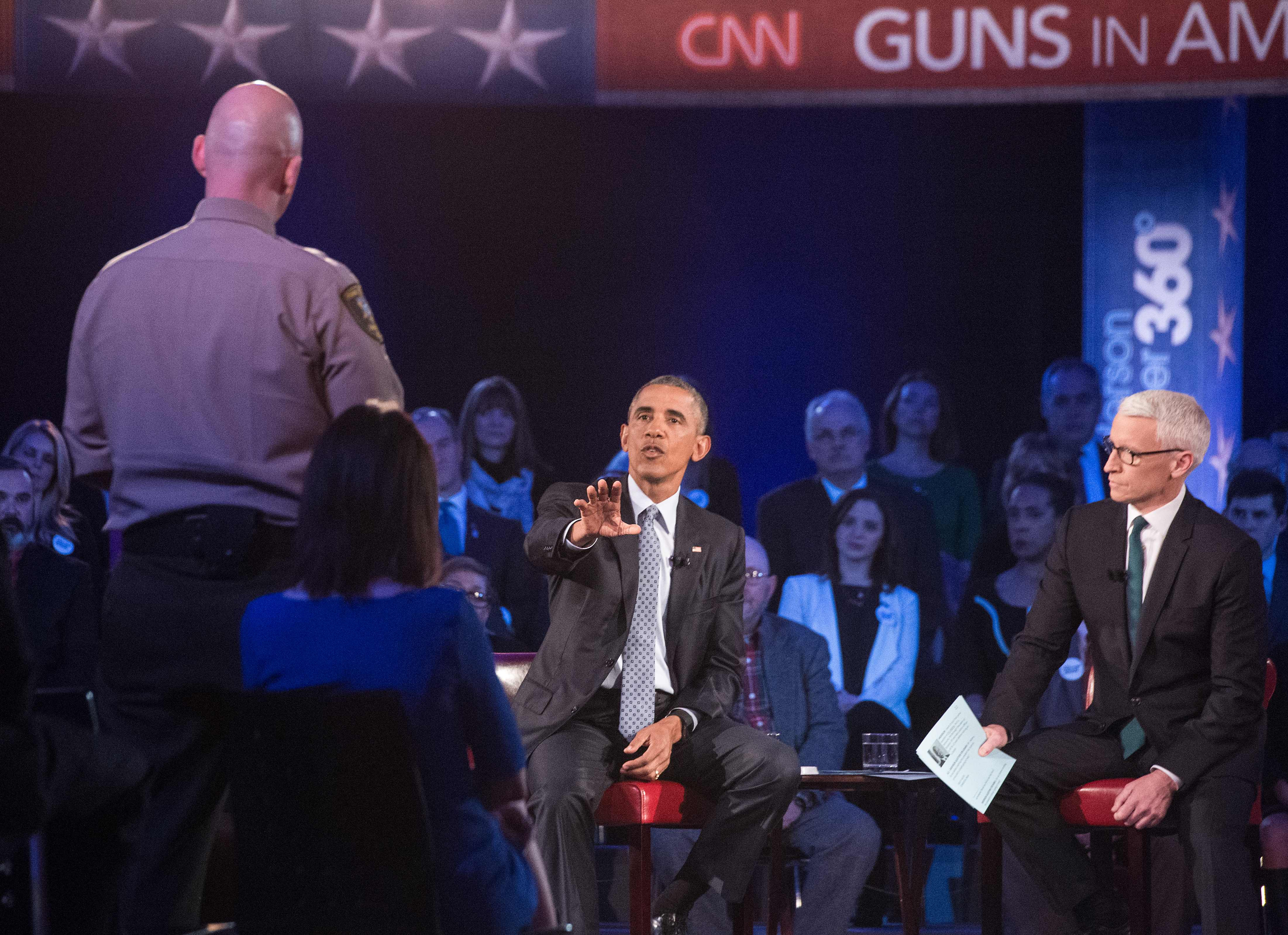 President Barack Obama replies to a question by Arizona Sheriff Paul Babeu (L) at a town hall meeting with CNN's Anderson Cooper (R) on reducing gun violence at George Mason University in Fairfax, Virginia, on January 7, 2016.