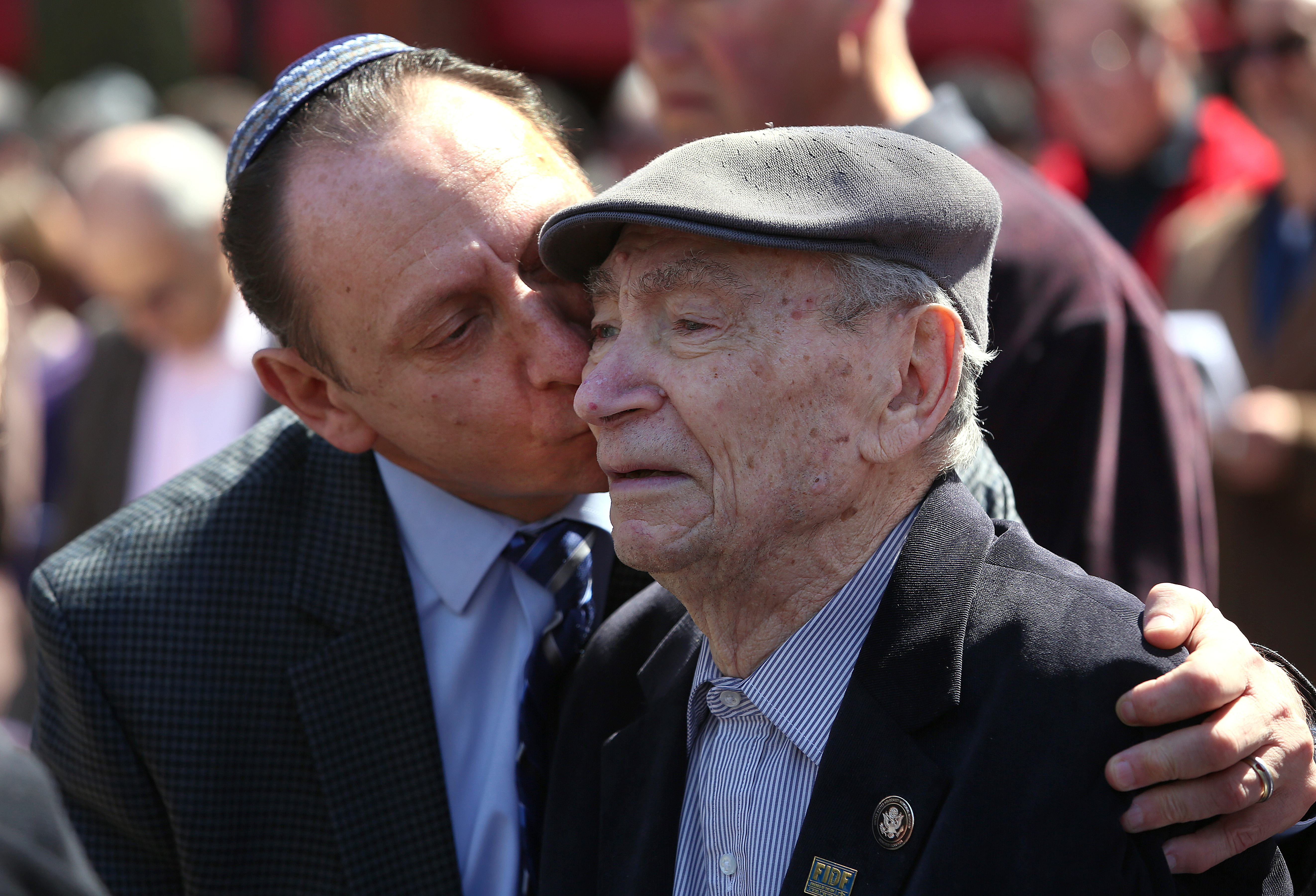 Mark Rogozinski kisses his 91-year-old father, Abram Rogozinski, who is a survivor of seven camps, at the New England Holocaust Memorial on April 12, 2015.