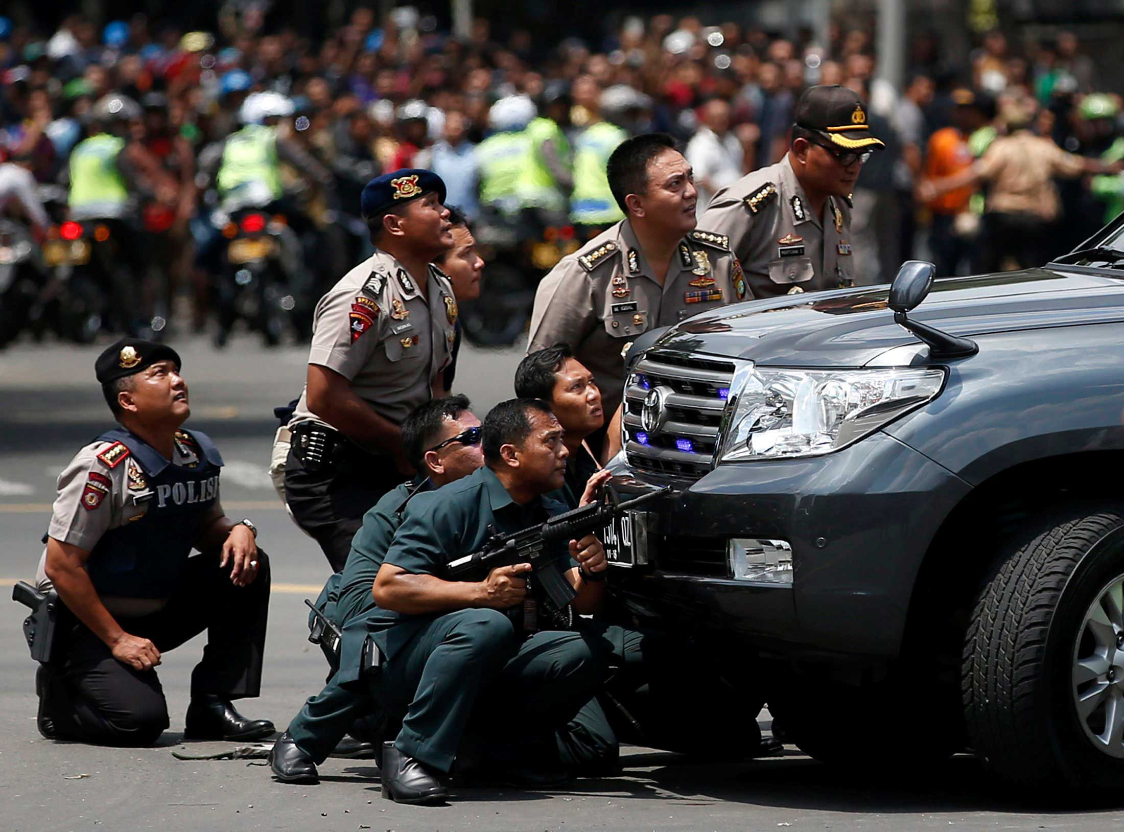 Police officers react near the site of a blast in Jakarta, Indonesia, Jan.14, 2016.