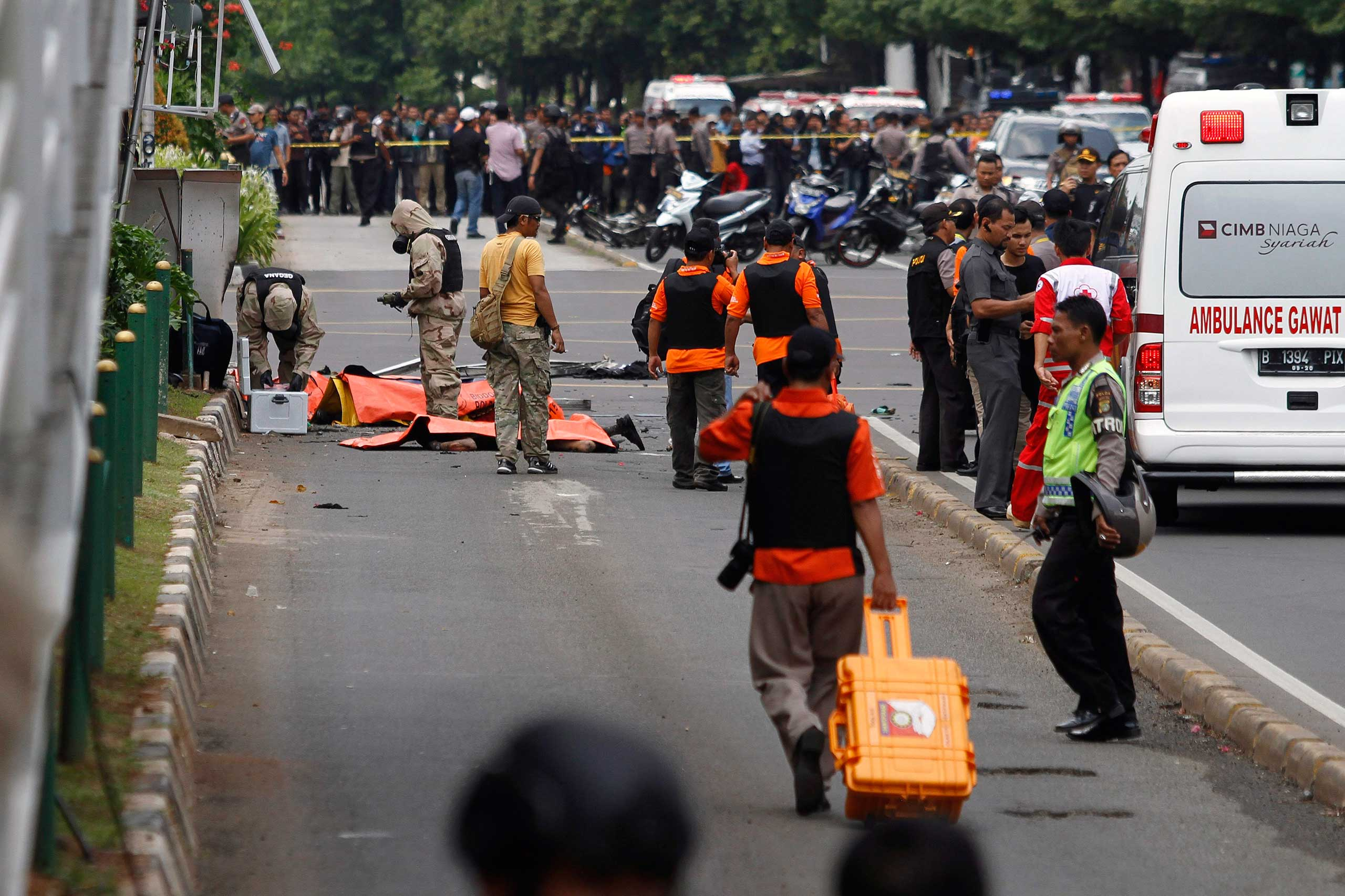 Special forces officers identify victims at the scene of a bomb blast in Jakarta, Indonesia, Jan. 14, 2016. Seven people, including several suspected attackers, died in bomb blasts and gunfire in the center of the Indonesian capital in what the country's president described as an act of terrorism.