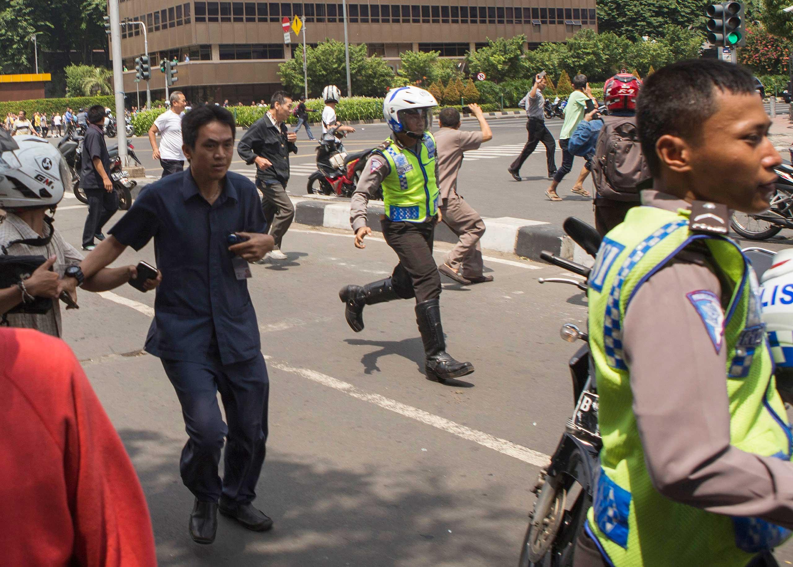 People flee from the scene after a gun battle broke out following an explosion in Jakarta, Indonesia, Jan. 14, 2016.